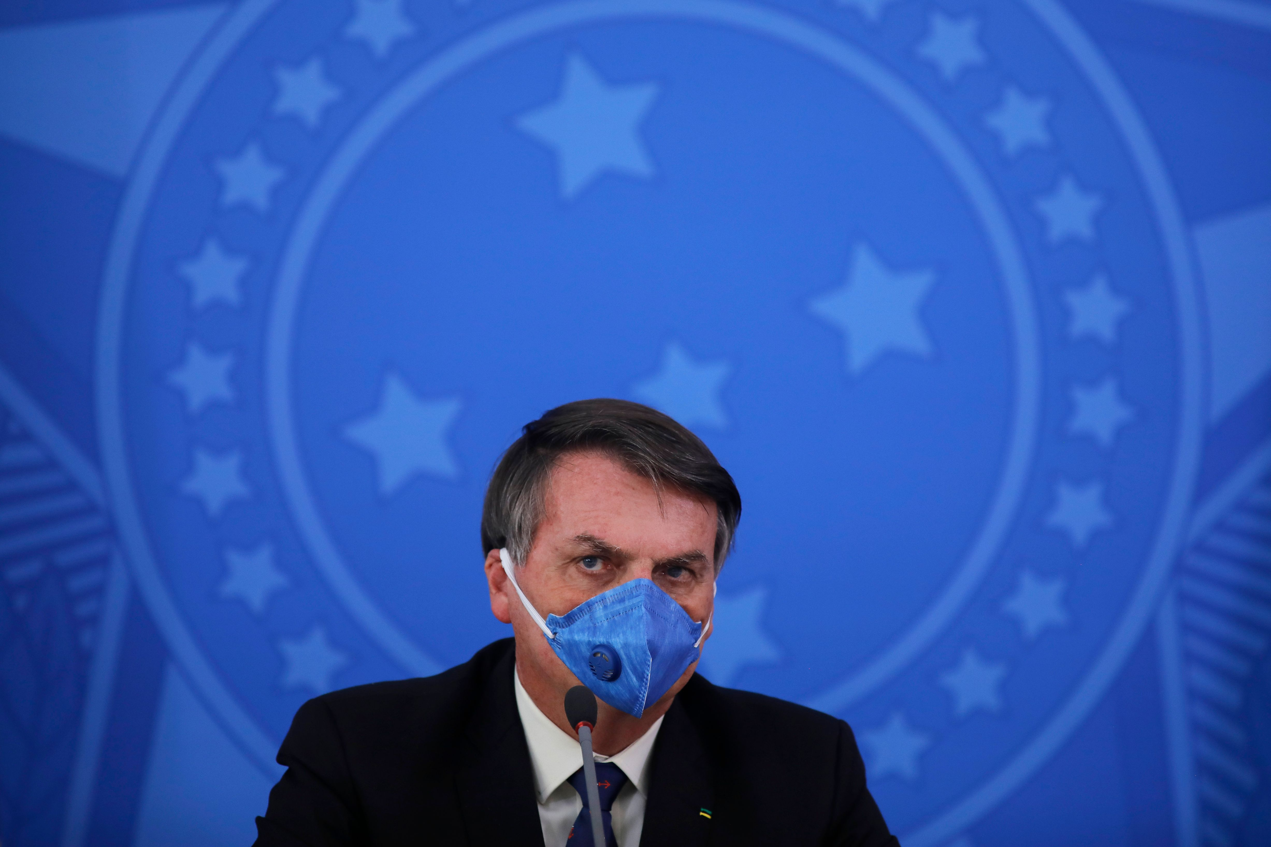 Brazil's President Jair Bolsonaro wears a face mask during a press conference on the coronavirus pandemic at the Planalto Palace in Brasilia, Brazil on March 20, 2020.