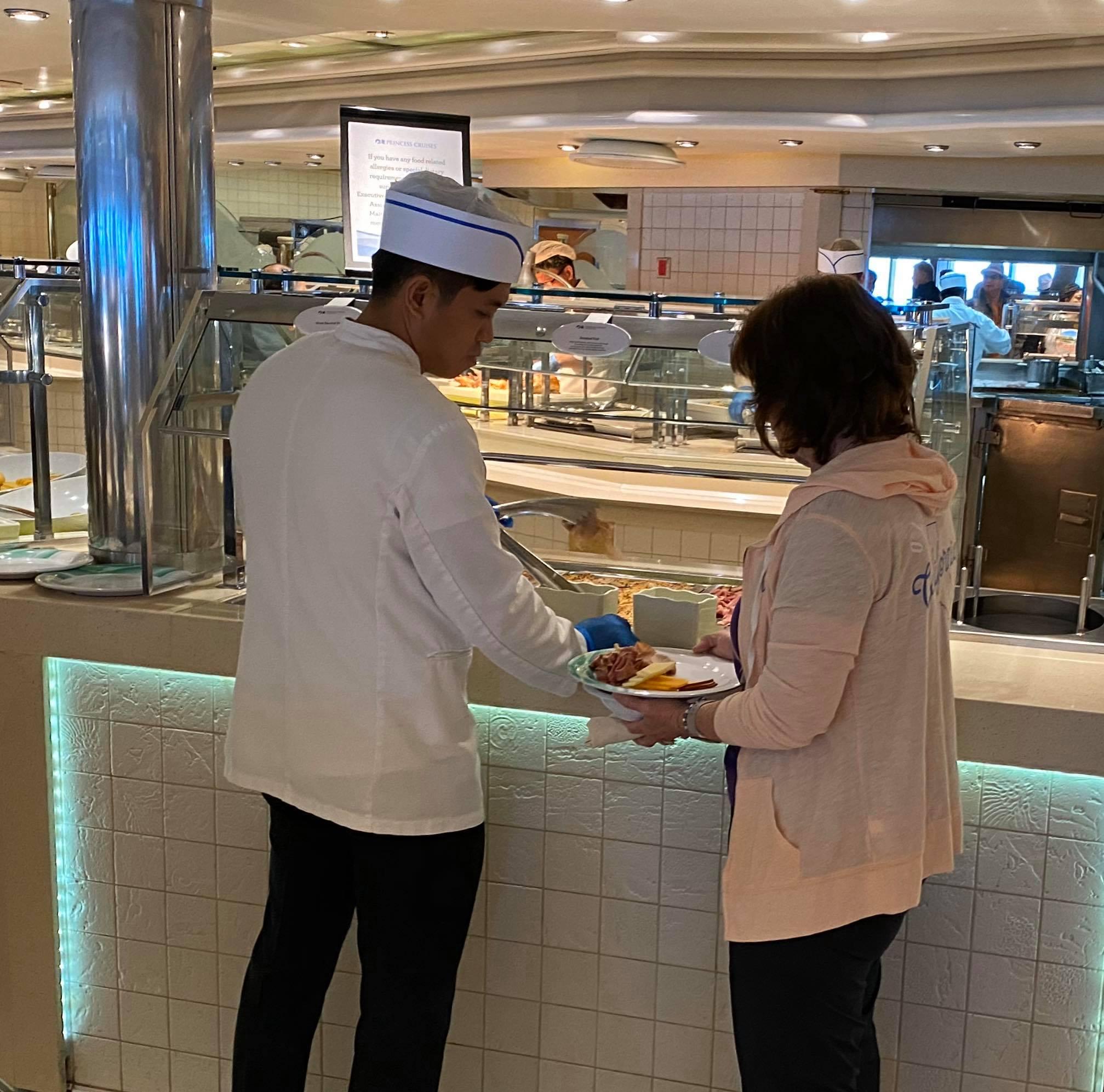A crew member serves passenger food at a buffet on Grand Princess on Mar. 5, 2020.
