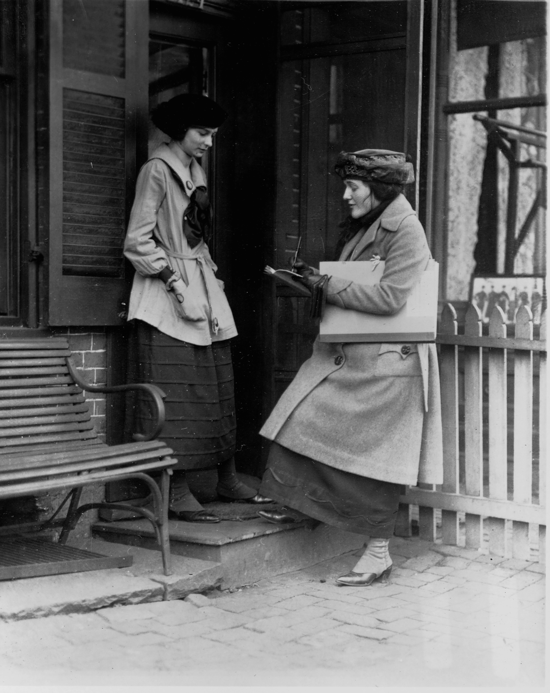 A Census taker asks questions of a woman at the door of her house, early 20th century.