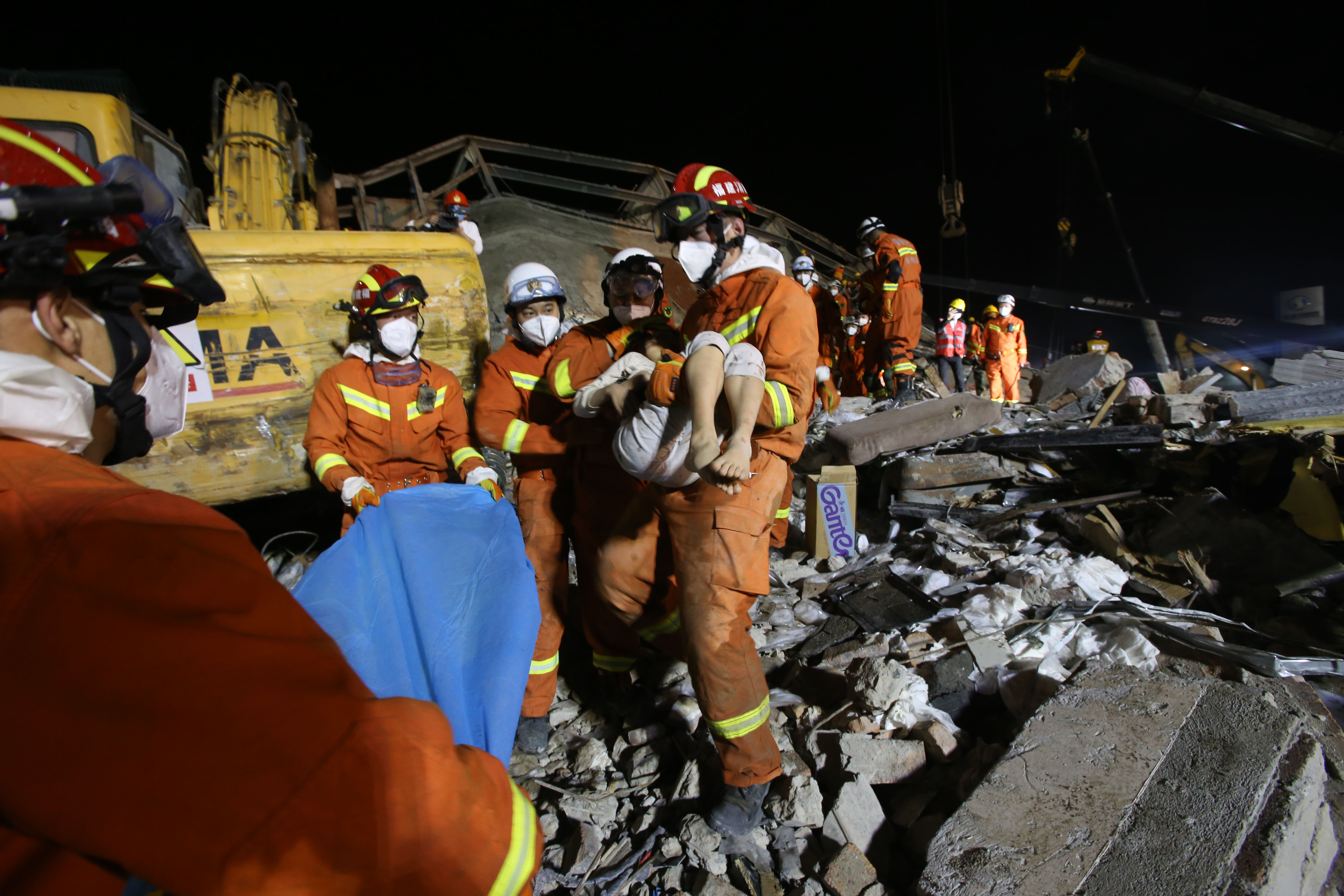 A rescuer carries a boy from the site of a hotel building collapse in Quanzhou on March 9, 2020.