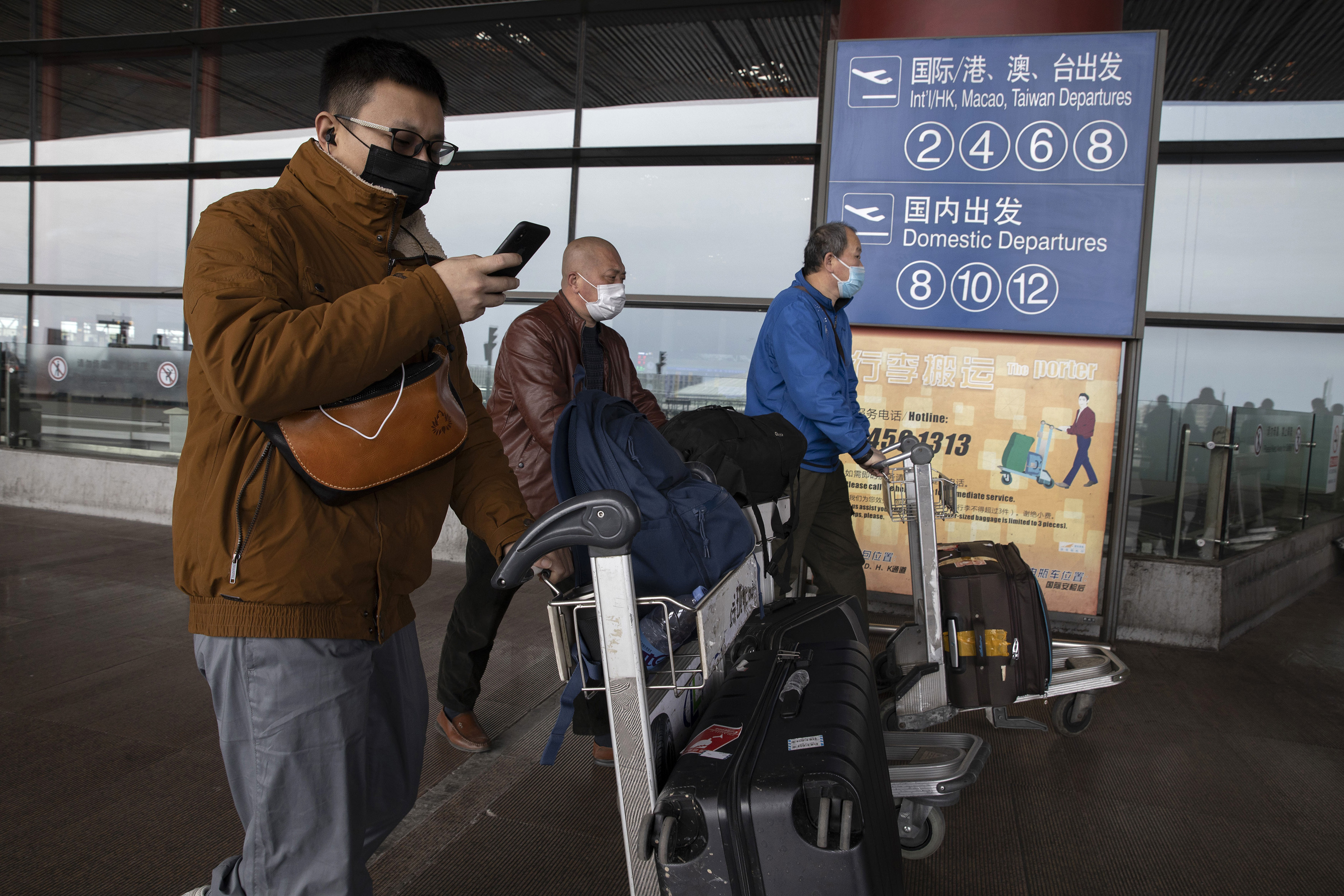 Travelers walk outside the Capital International Airport terminal 3 in Beijing on March 12, 2020.