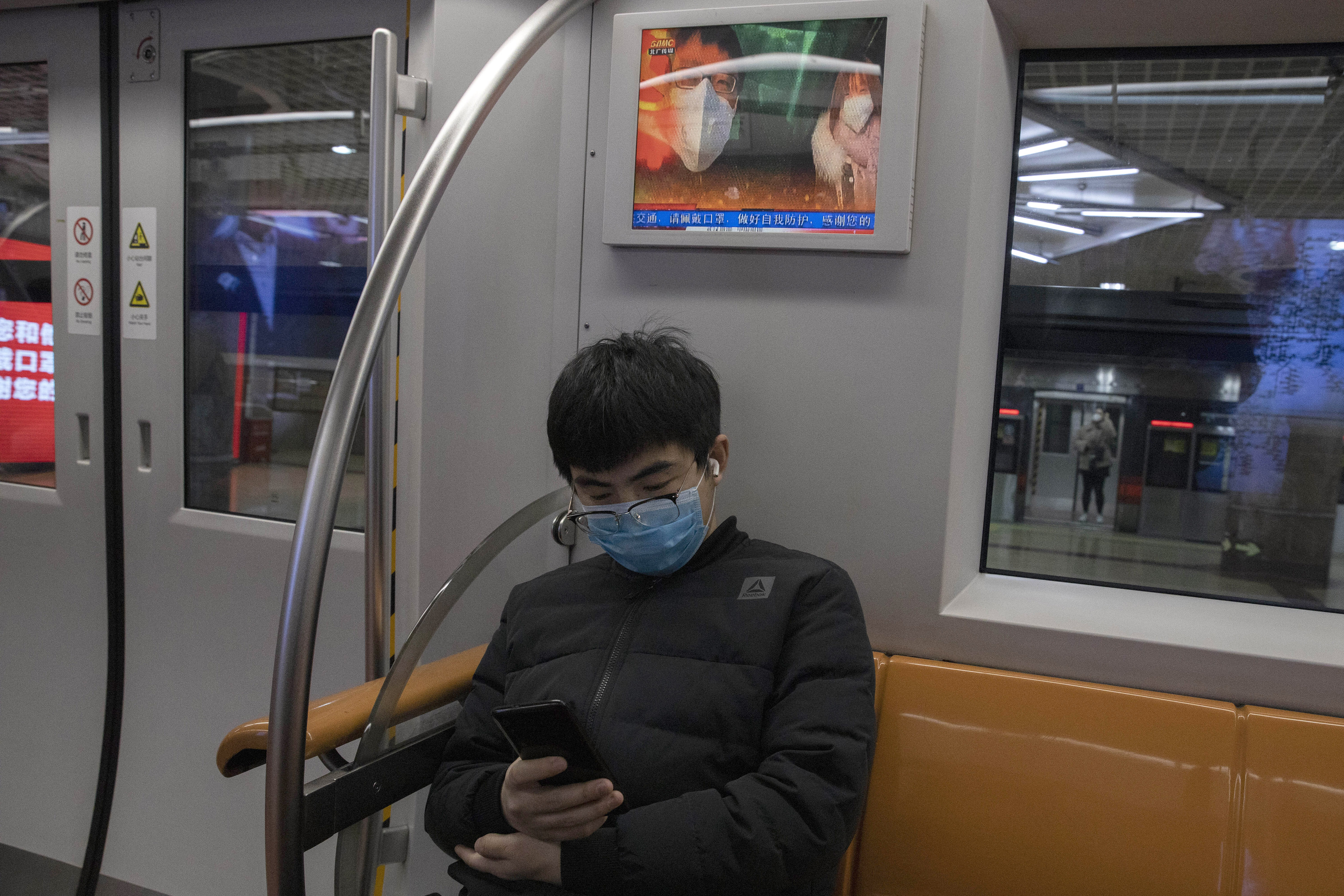 A passenger sits under a public information display encouraging the use of mask on a subway train in Beijing Monday, March 9, 2020. With almost no new COVID-19 cases being reported in Beijing, workers are slowly returning to their offices with masks on and disinfectant in hand. But officials remain cautious, torn between wanting to restart the economy and fear of a resurgence of the outbreak.