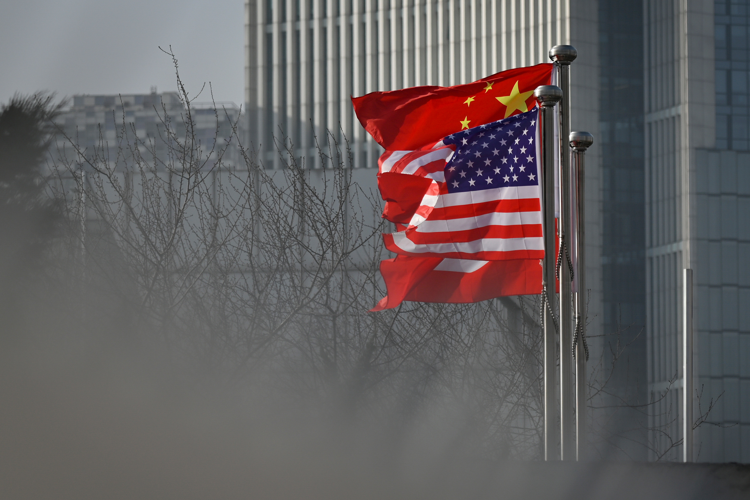 Chinese and U.S. national flags flutter at the entrance of an office building in Beijing on Jan. 19, 2020.