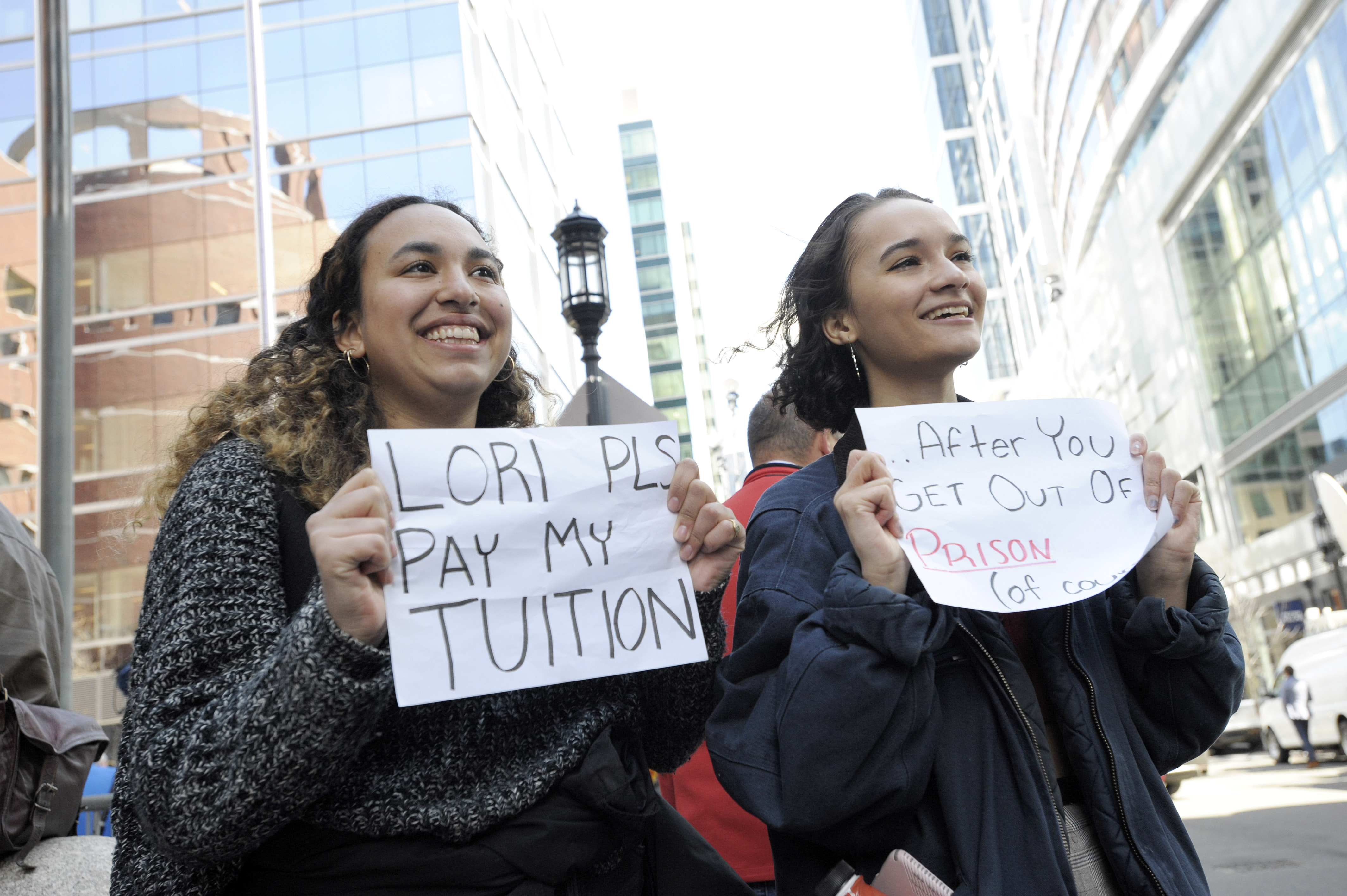 Mackenzie Thomas and Vivi Bonomie hold signs outside federal court in Boston, where actor Lori Loughlin was facing criminal charges related to a college admissions scandal, on April 3, 2019.