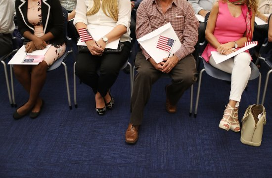 People hold an American flags as they participate in a ceremony to become an American citizen