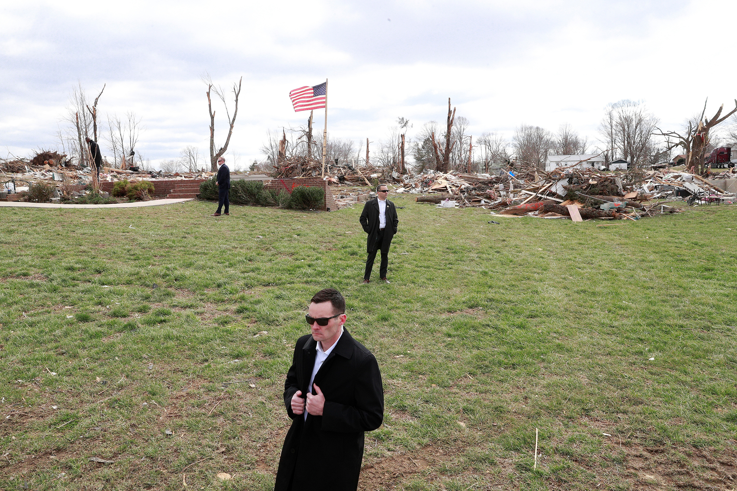 U.S. Secret Service agents stand by as President Trump, not pictured, observes tornado damage in Cookeville, east of Nashville, on March 6, 2020.