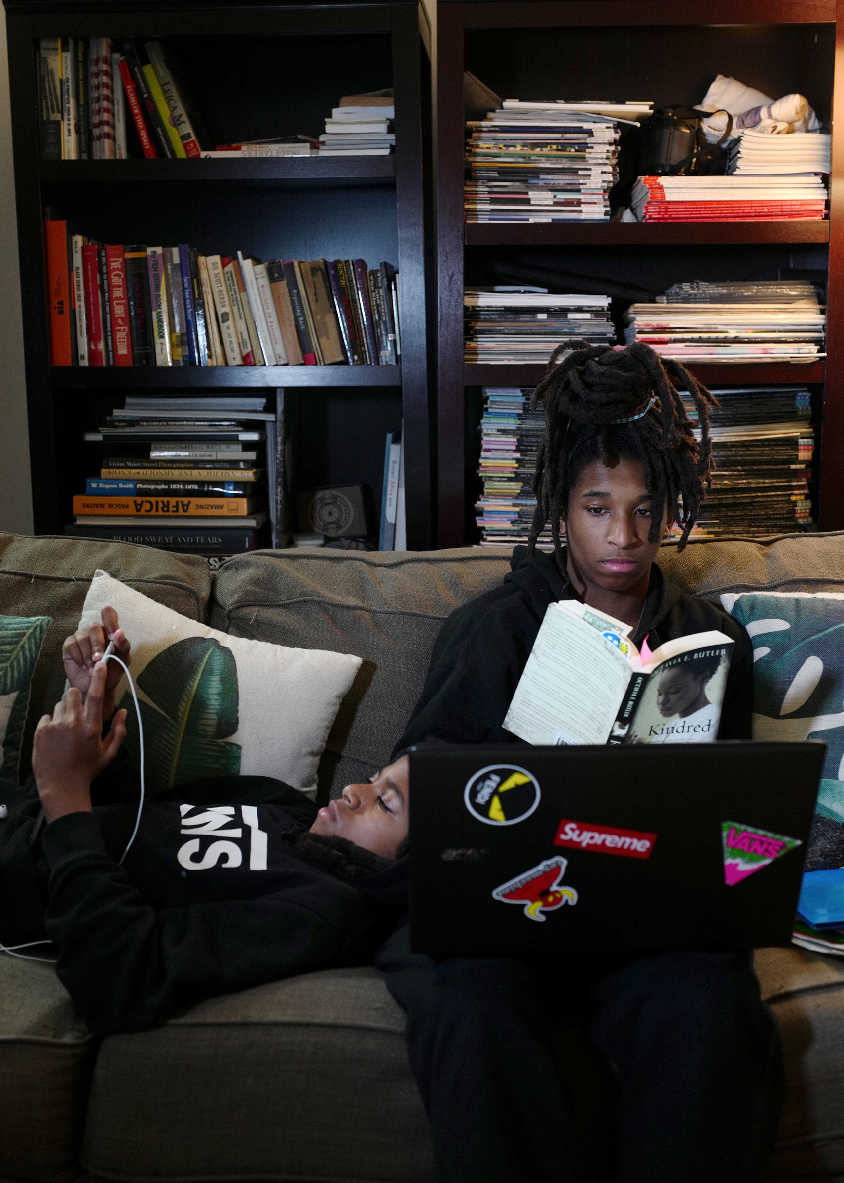 Mosijah Roye, 15, right, and Iyeoshujah, 11, the photographer's sons, follow online classes in New York on March 23 on their home devices