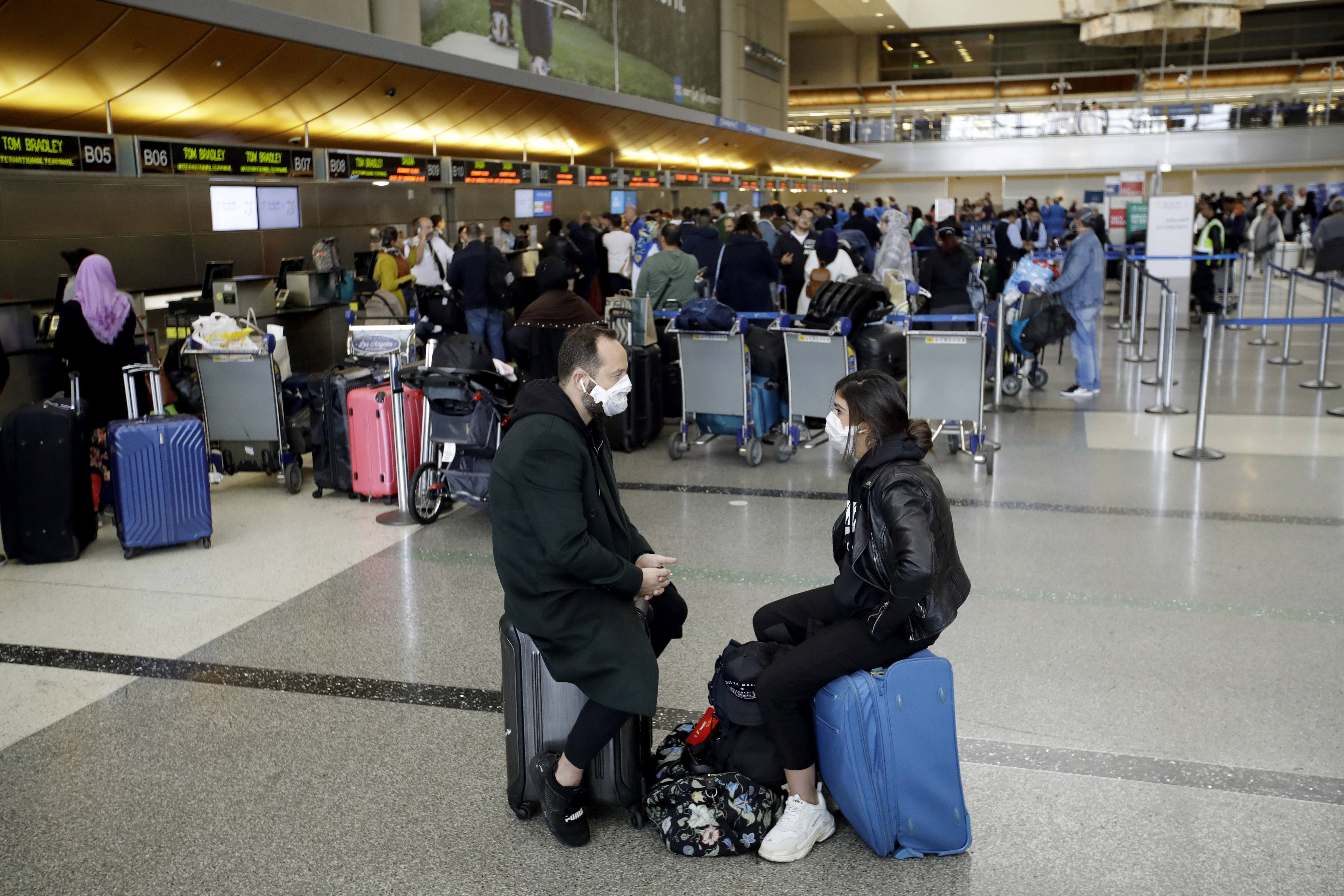 In this Saturday, March 14, 2020 file photo, travelers wait to check in their luggage at the Los Angeles International Airport. The coronavirus pandemic that's caused many Americans to avoid airports has others booking spur-of-the moment trips at dirt-cheap ticket prices.