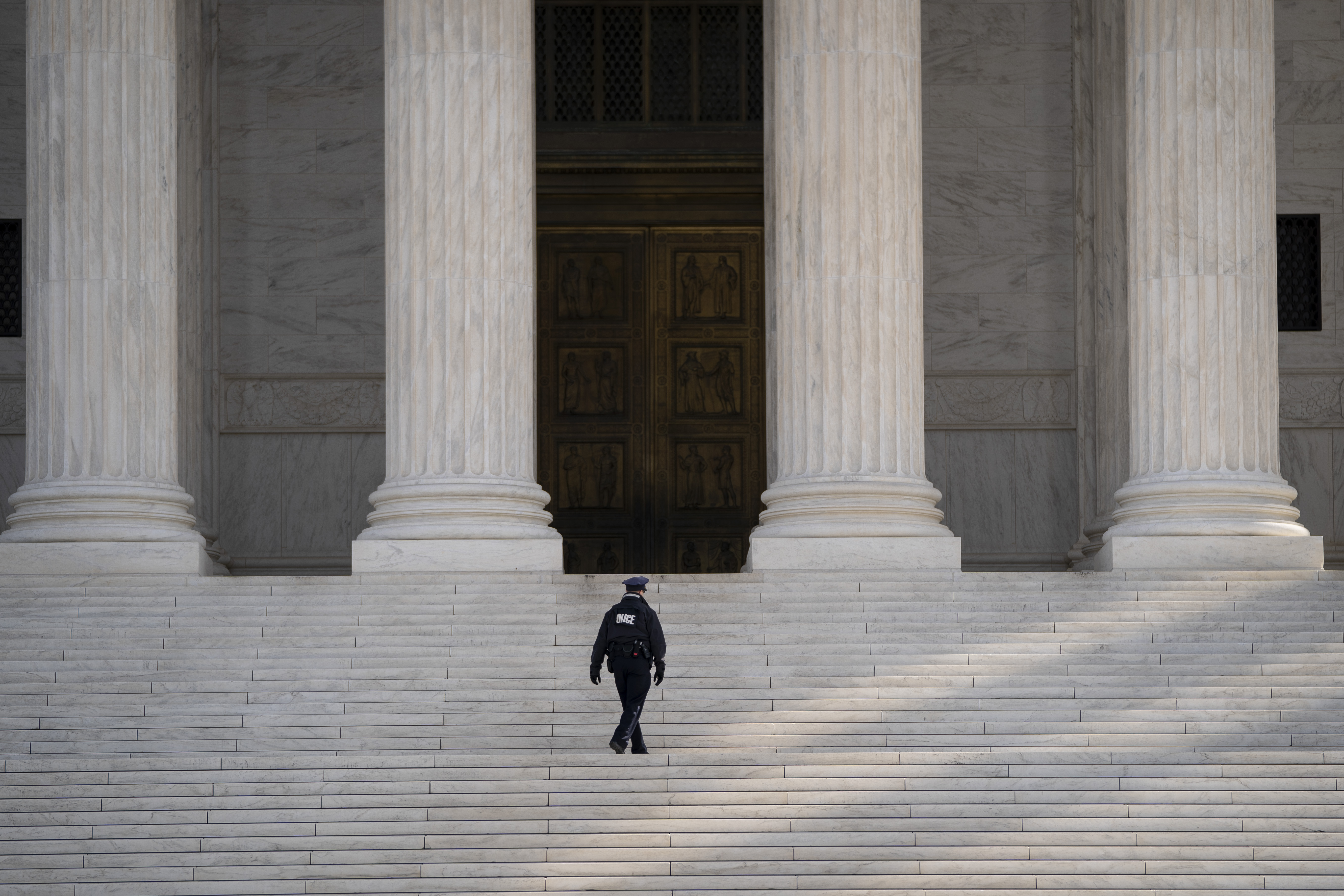 A Supreme Court police officer walks up the steps at the U.S. Supreme Court on March 16, 2020 in Washington, DC.