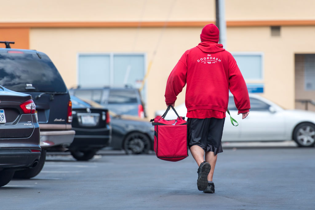 A DoorDash Inc. delivery person carries an order bag outside of a DoorDash Kitchens location in Redwood City, California, U.S., on Friday, Nov. 29, 2019