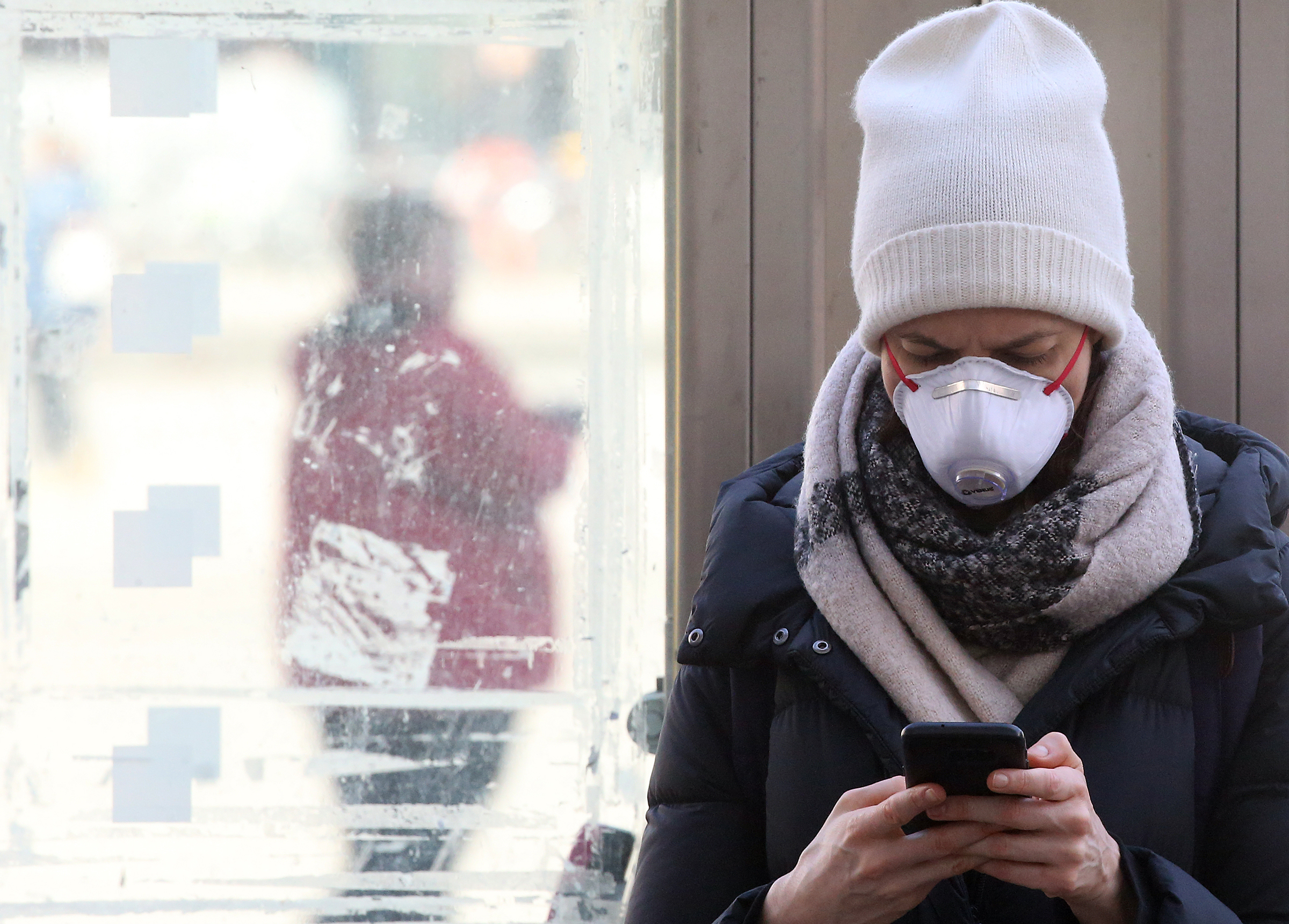A young woman wearing a mask uses her smartphone to obtain information on the news situation regarding the corona virus at Alexanderplatz in Berlin on March 16, 2020.