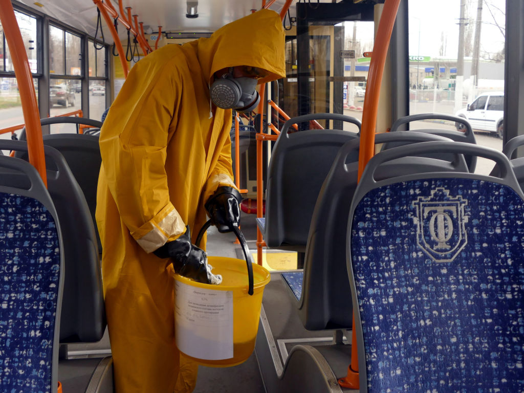 A man in a chemical protection suit and respirator sanitizes seats and handrails on a public transport vehicle to prevent the spread of the novel coronavirus in Odessa, Ukraine.