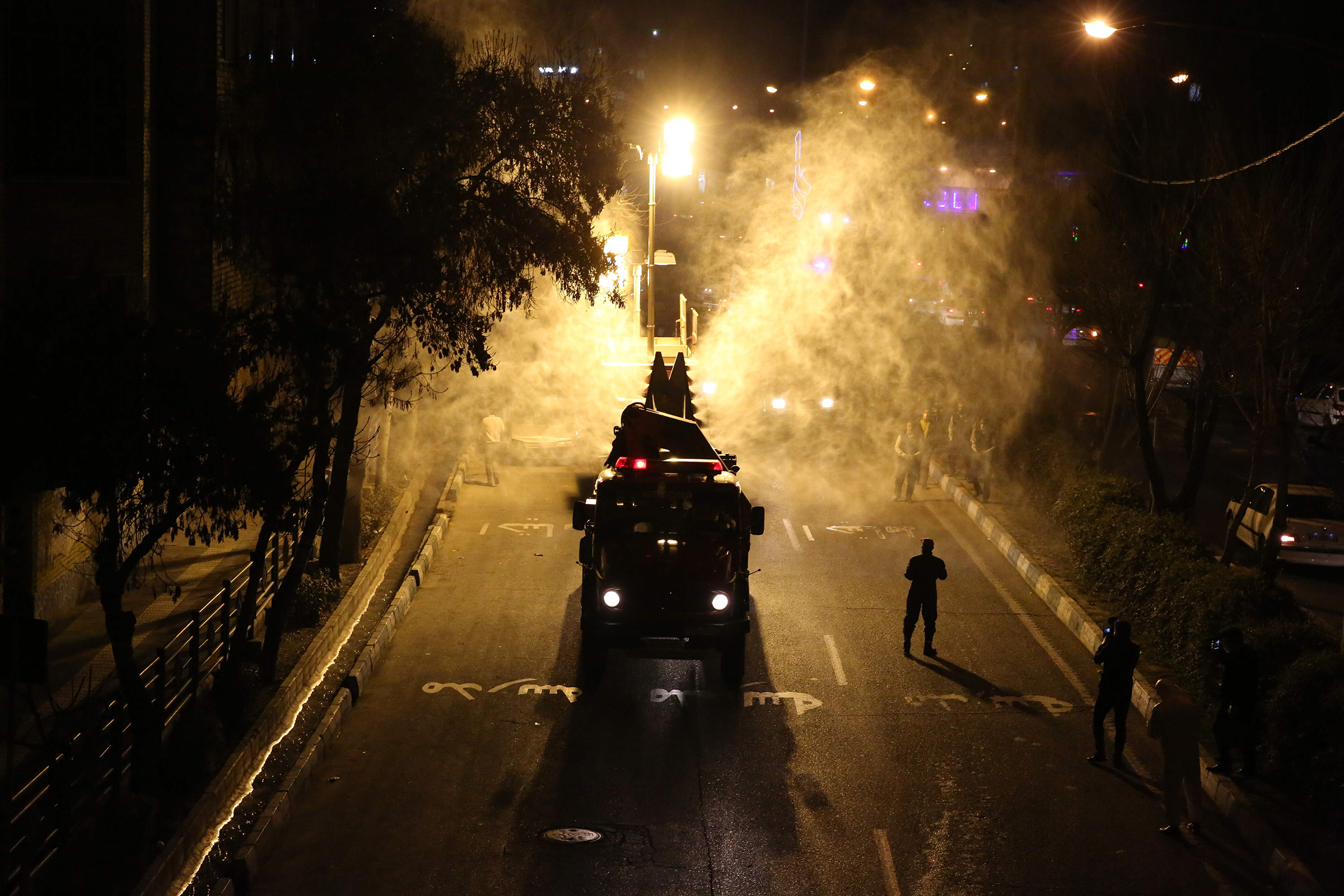 Iranian firefighters disinfect streets and allies in southern Tehran to halt the wild spread of coronavirus on March 11