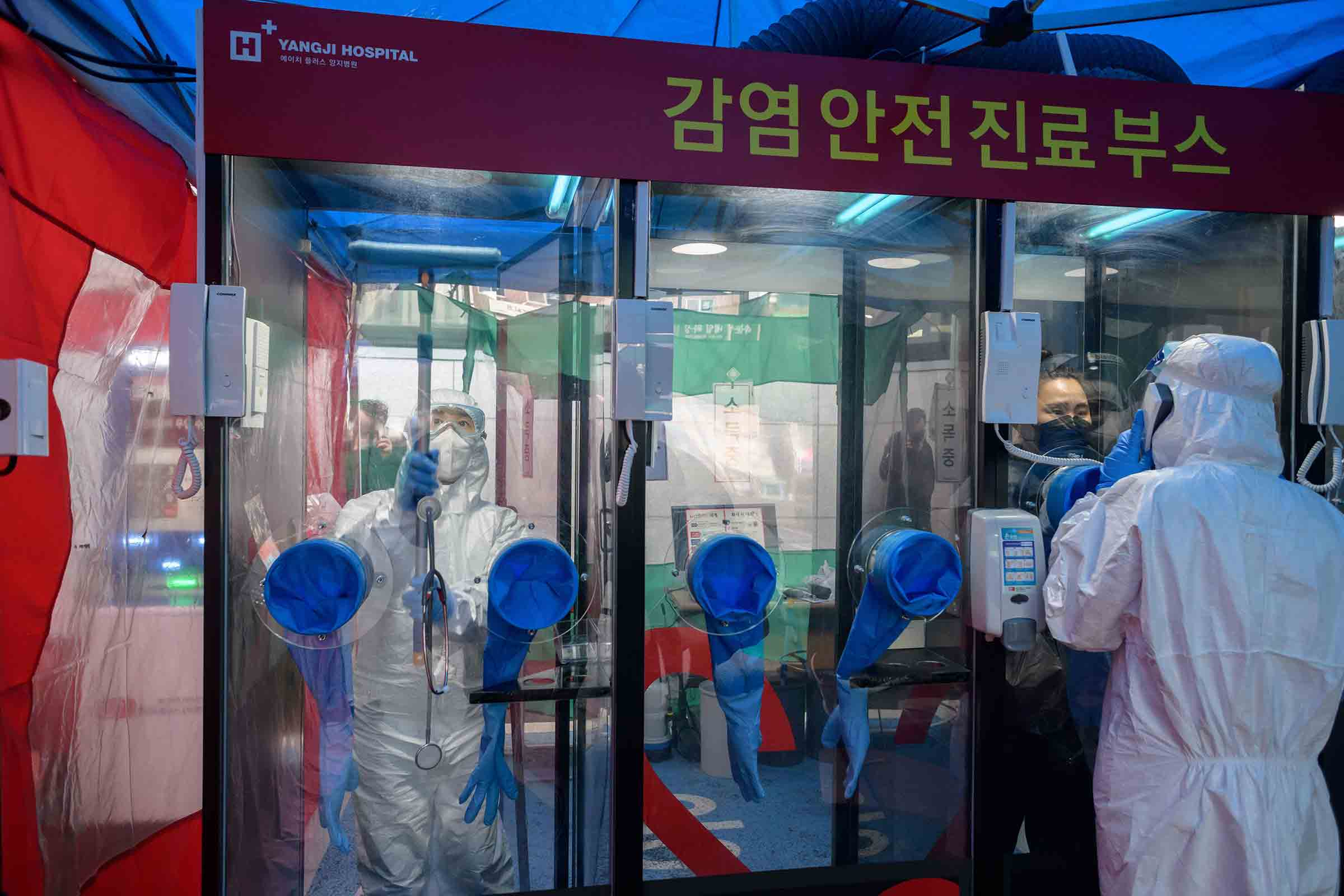 A woman consults a nurse at a walk-up COVID-19 testing booth outside Yangji Hospital in Seoul