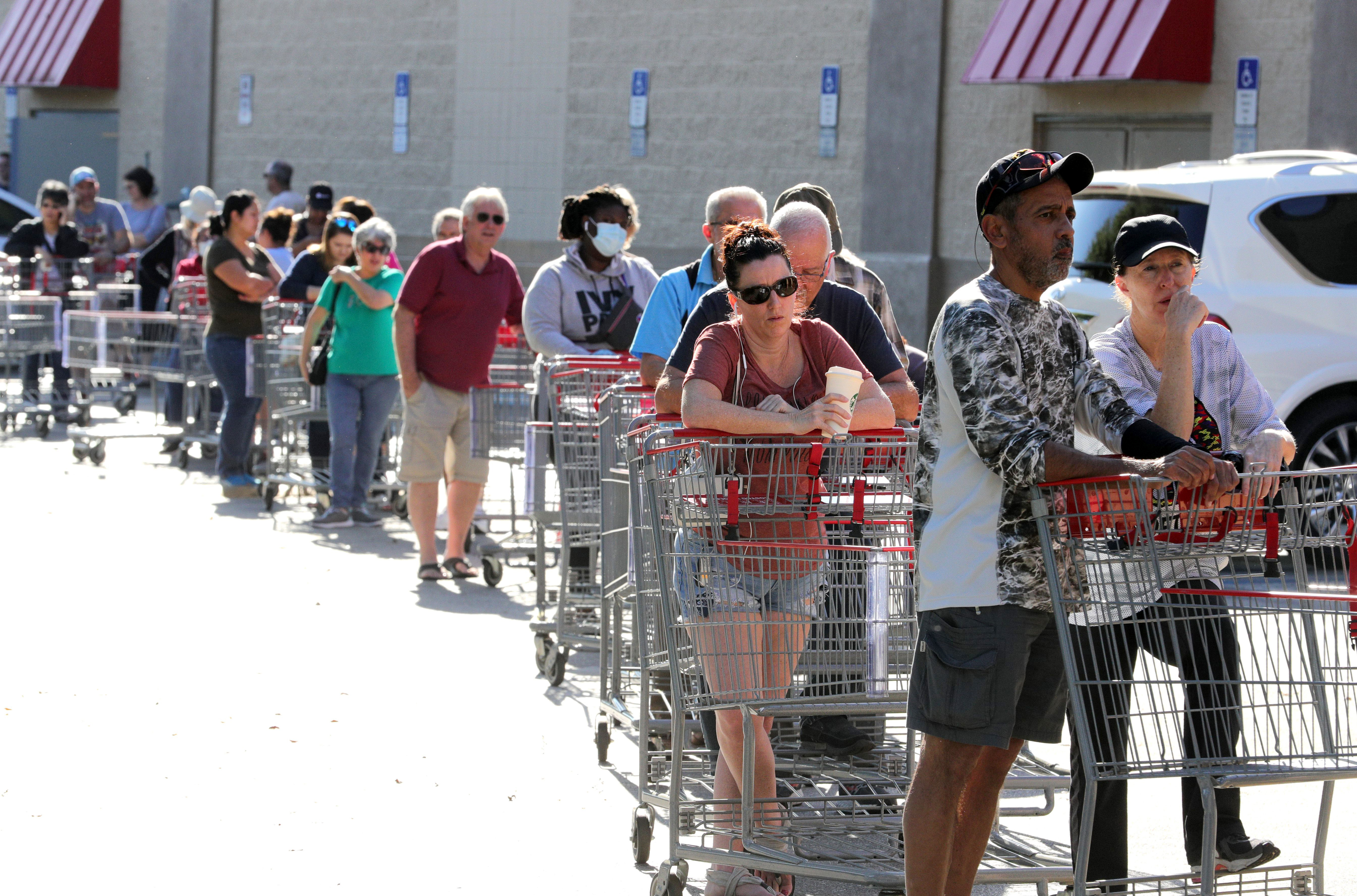 Hundreds of shoppers wait in line outside a Costco in Altamonte Springs, Fla., on March 19, 2020. The store was out of stock on hand sanitizer, toilet paper, bleach and other high-demand sanitation products as a result of the coronavirus response.