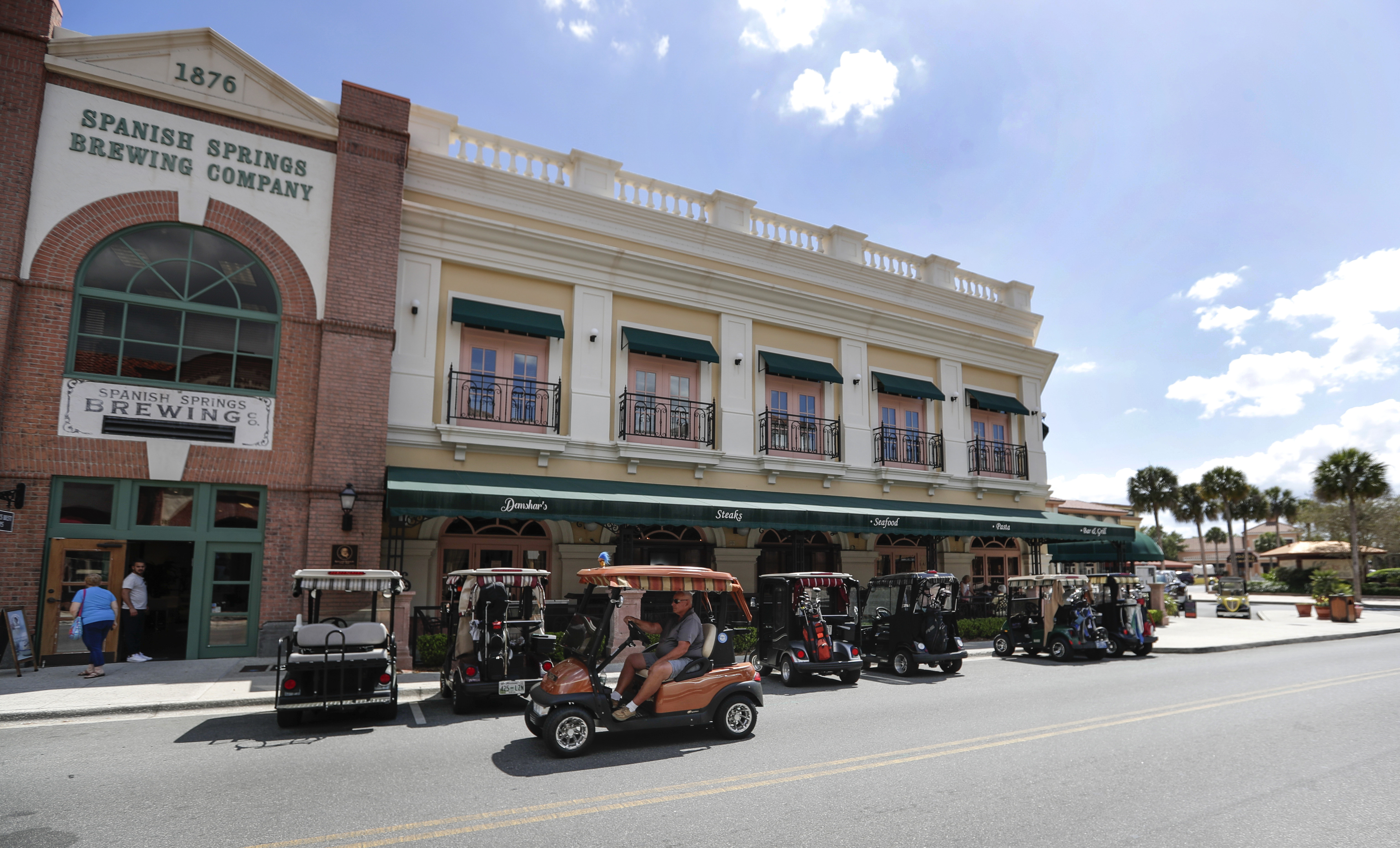 In this Thursday, March 19, 2020 photo, golf carts are lined up outside one of the few open restaurants in The Villages, Fla., as three town squares closed due to the coronavirus through the end of the month.