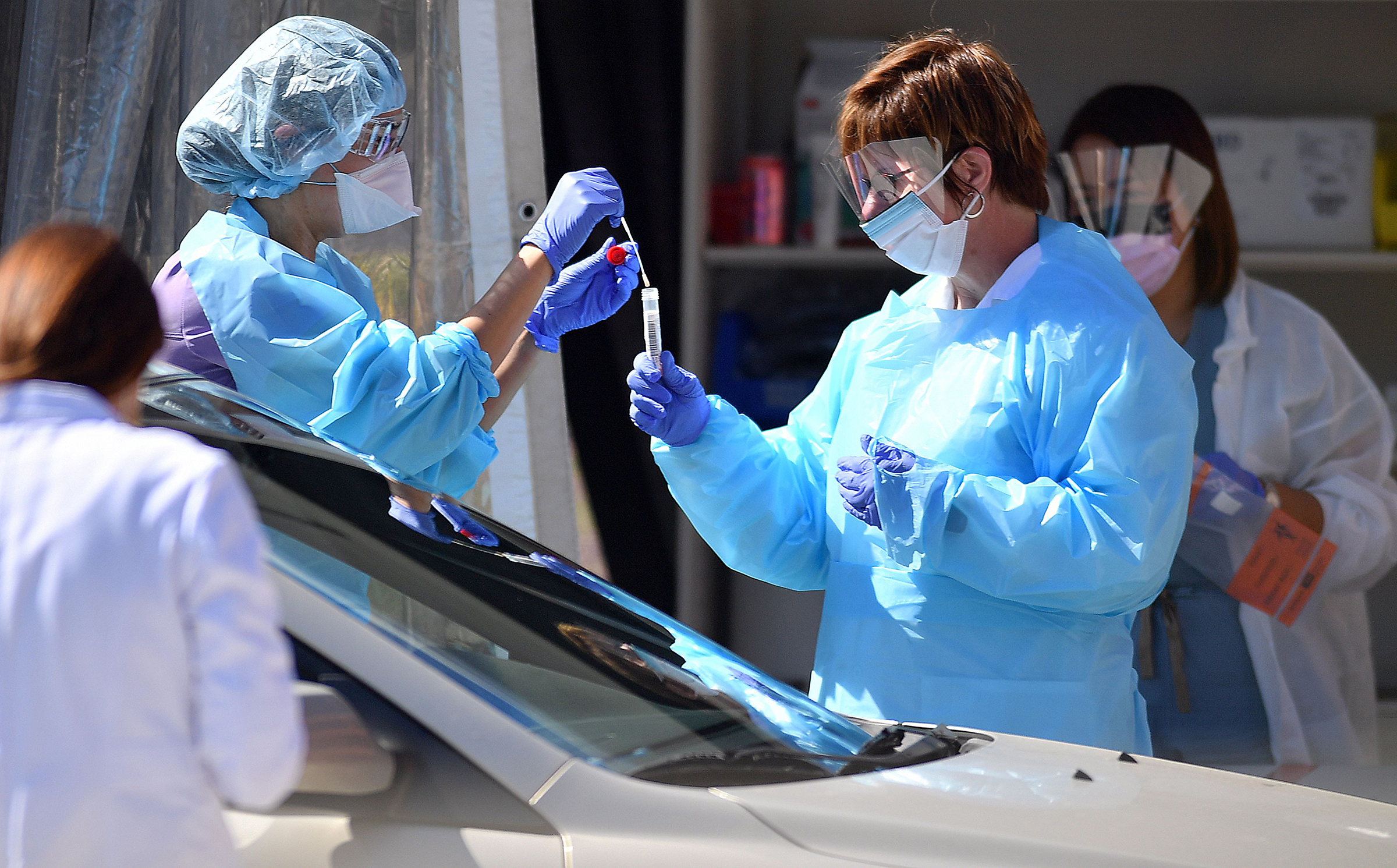 Medical workers test a patient for the novel coronavirus, COVID-19, at a drive-thru testing facility in San Francisco, California on March 12, 2020.