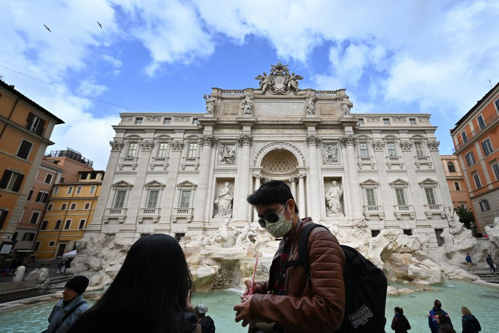 Tourists wear protective masks  in front of the Trevi fountain in Rome on March 3, 2020.
