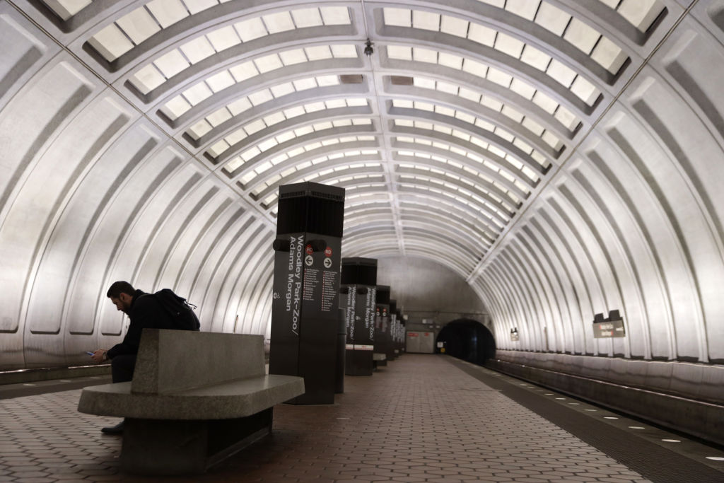 A passenger waits for his train at an almost empty platform at Woodley Park-Zoo/Adams Morgan Metro station in Washington, D.C. on Mar. 16, 2020.