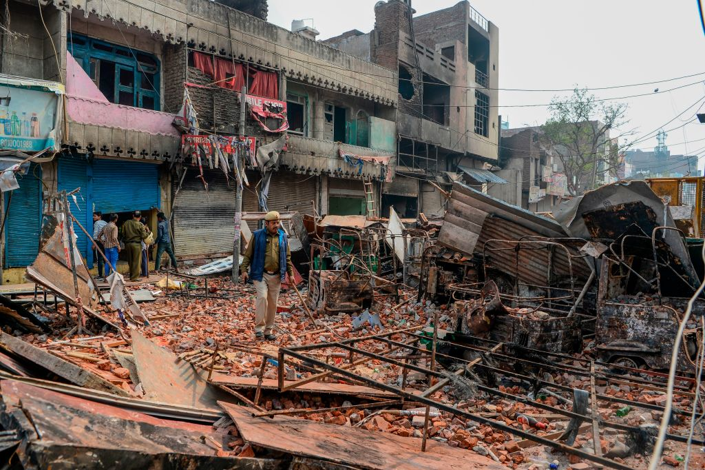 Security personnel patrol near burnt-out and damaged residential premises and shops in New Delhi on February 26, 2020.