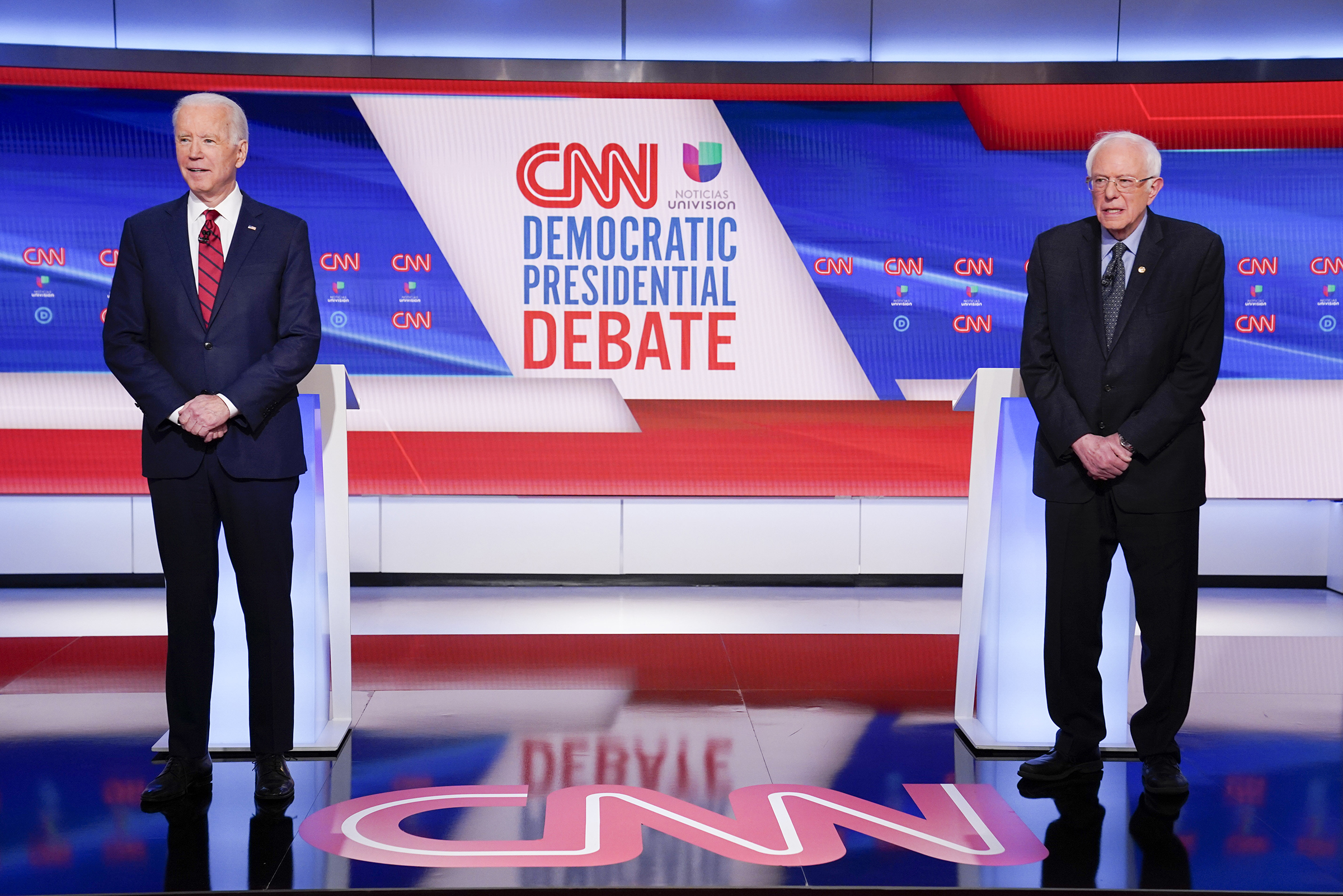 Former Vice President Joe Biden, left, and Sen. Bernie Sanders, I-Vt., right, wait on stage to participate in a Democratic presidential primary debate in Washington D.C. on March 15, 2020.
