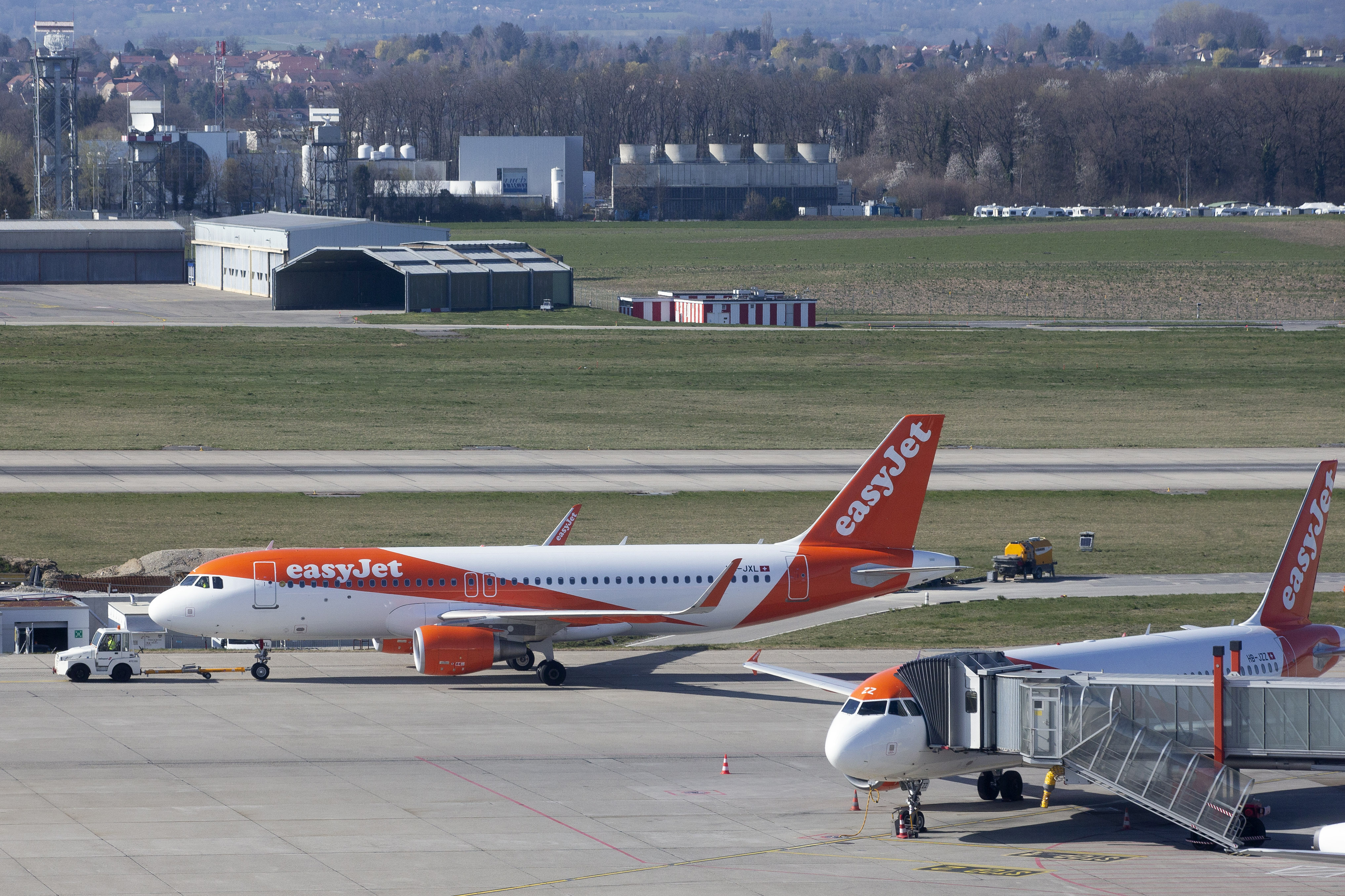 An easyJet aircraft is towed on the tarmac of the Geneve Aeroport, in Geneva, Switzerland on March 24, 2020.