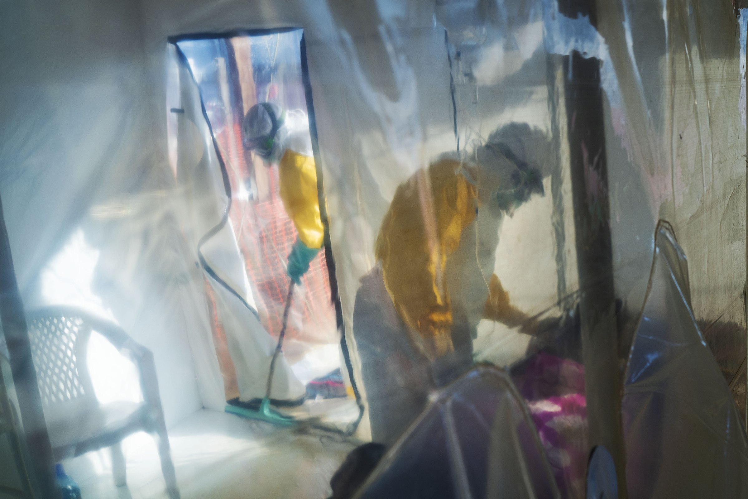 Health workers wearing protective suits tend to an Ebola victim kept in an isolation cube in Beni, Congo on March 13, 2019.