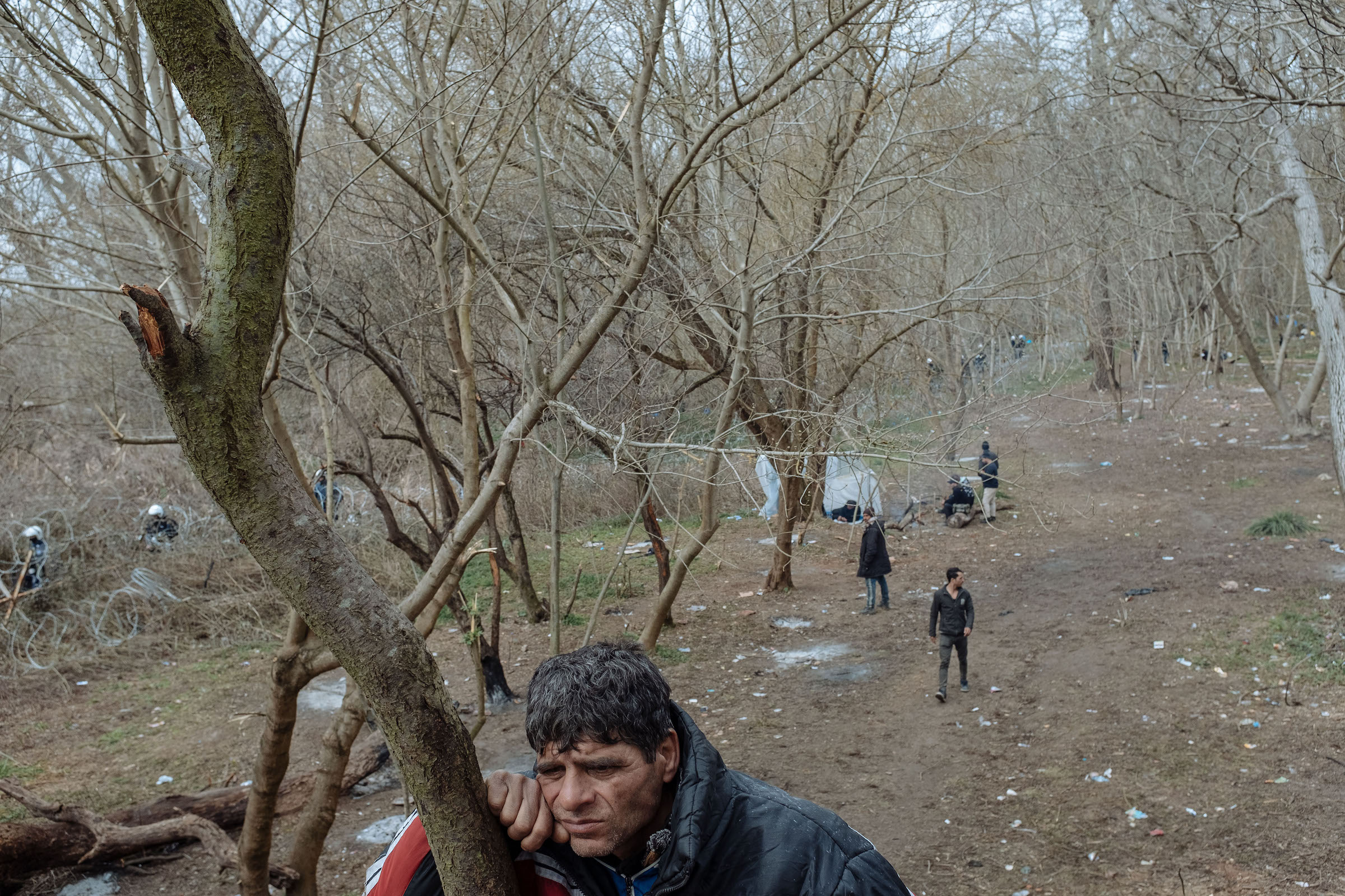 Muhammed, who fled Syria three years ago and was living in the Turkish port city of Mersin, rests against a tree.