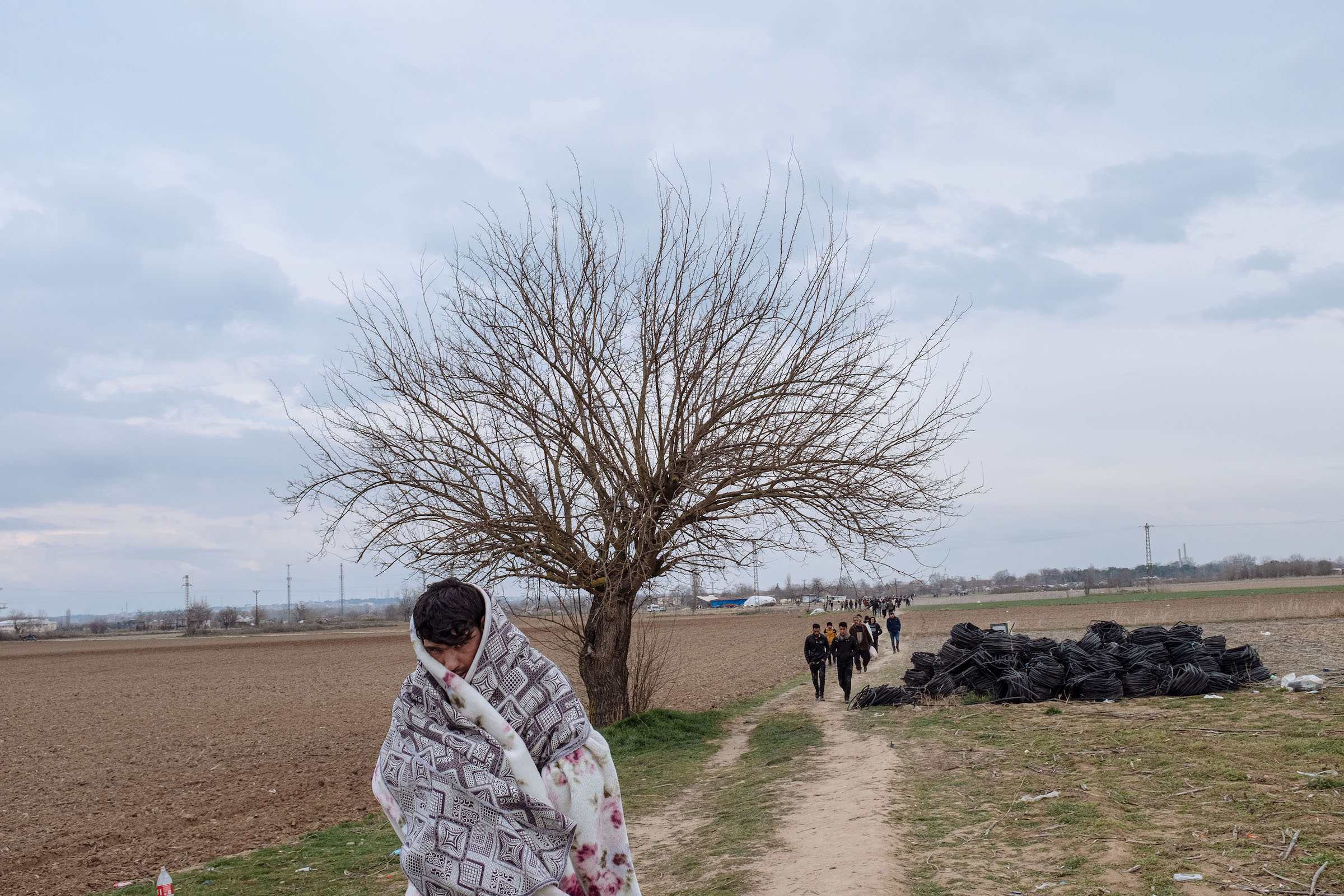 Migrants walk through a field toward the Turkey-Greece border.