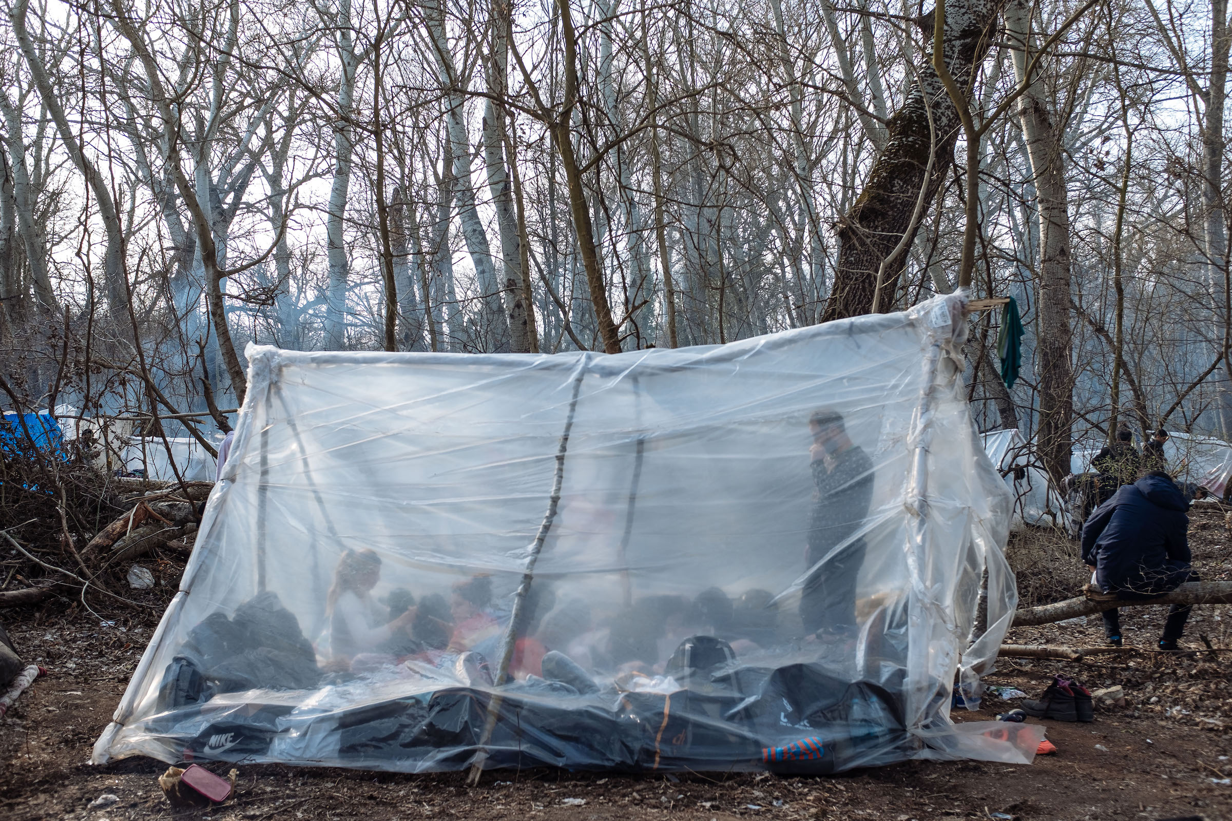 A tent made of propped-up branches, wrapped in plastic. Many migrants slept in the area for days, waiting for a chance to cross the border.