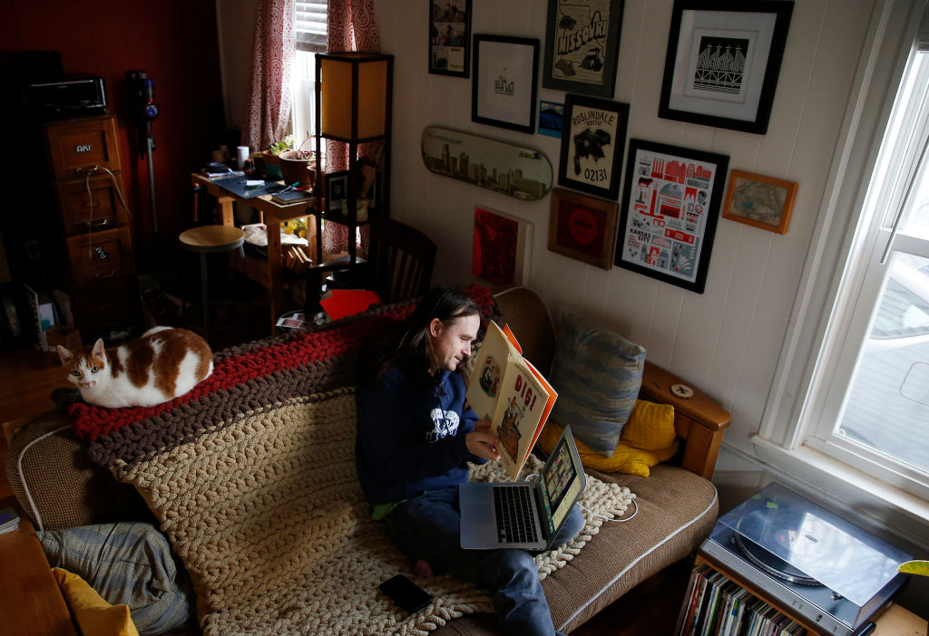 Kindergarten teacher Jamie Jones OBrien reads a children's book to his students as he  conducts a Zoom video lesson from his living room in Roslindale, MA on March 24, 2020.
