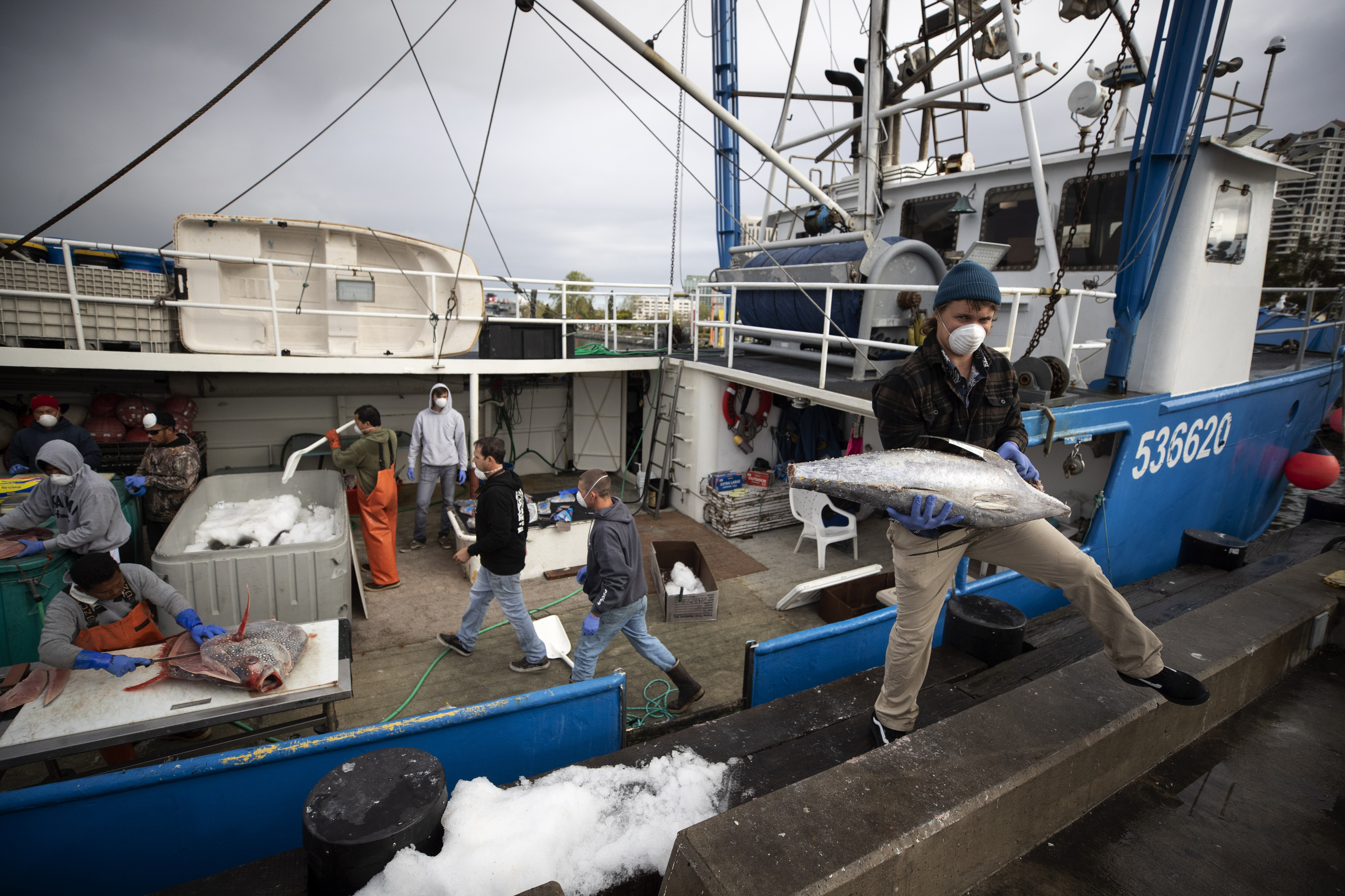 Fishing boat captain Nick Haworth, right, carries tuna to a dock for sale on March 20, 2020, in San Diego.