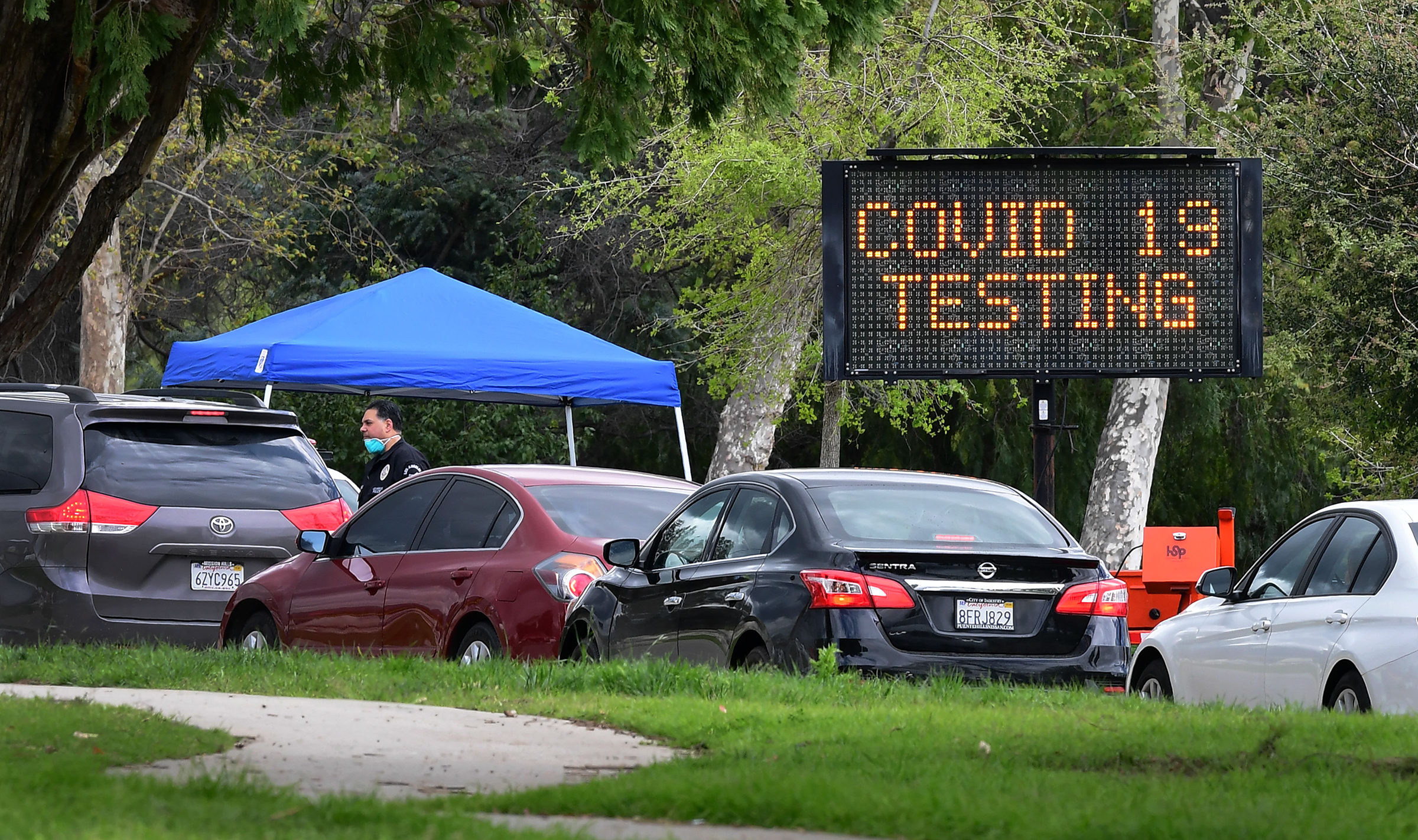 A police officer mans the entrance to a coronavirus  testing center in Hansen Dam Park on Mar. 25 in Pacoima, CA