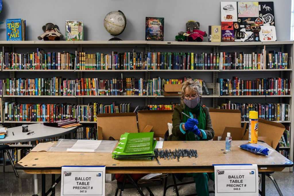 An election worker wears protective gloves during the Florida primary election at South Pointe Elementary School in Miami, on March 17, 2020.