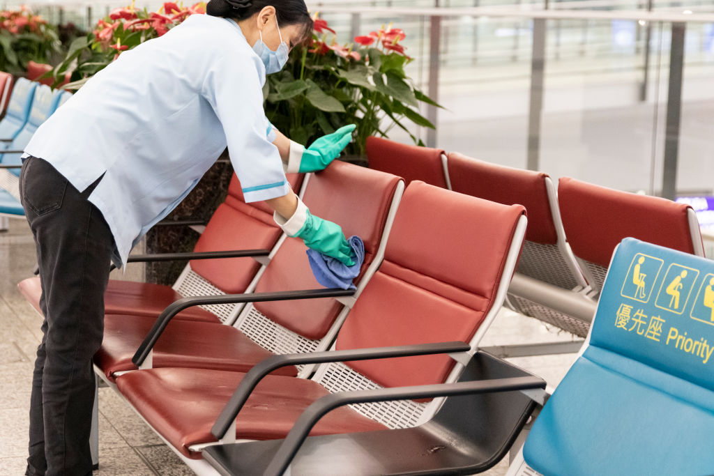 A cleaner wipes down chairs at the departure hall in Hong Kong International Airport in Hong Kong on Mar. 19, 2020.