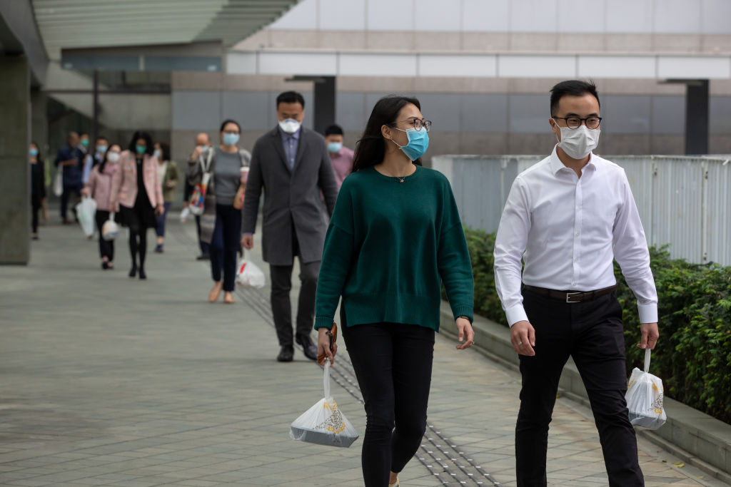 Office workers wearing masks carry take-out lunch orders while walking towards in Admiralty, Hong Kong, on Mar. 2, 2020.