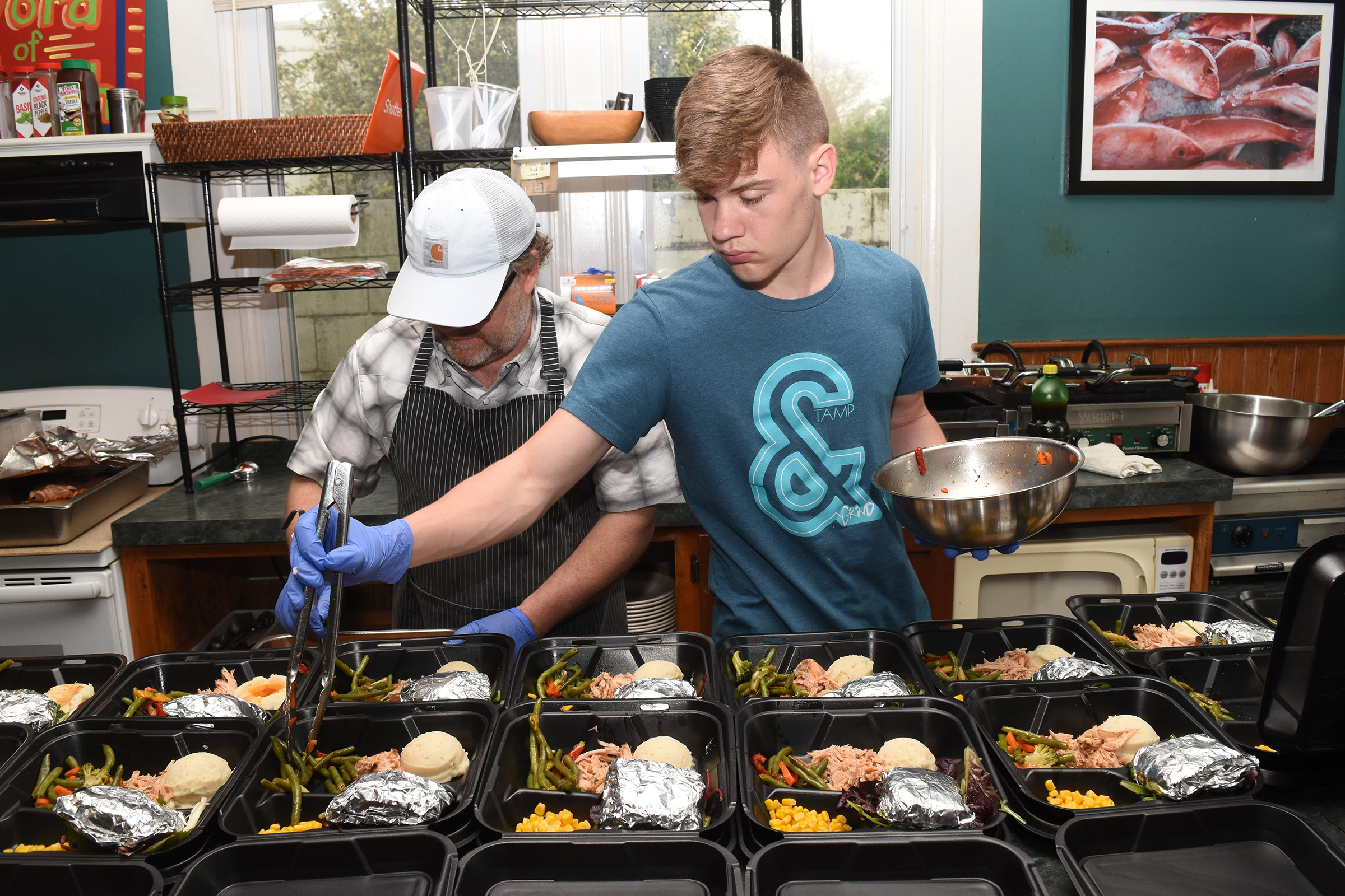 John Foster Gunter, owner of Word of Mouth Café in Louisiana, and his sons prepare free plate lunches for the elderly