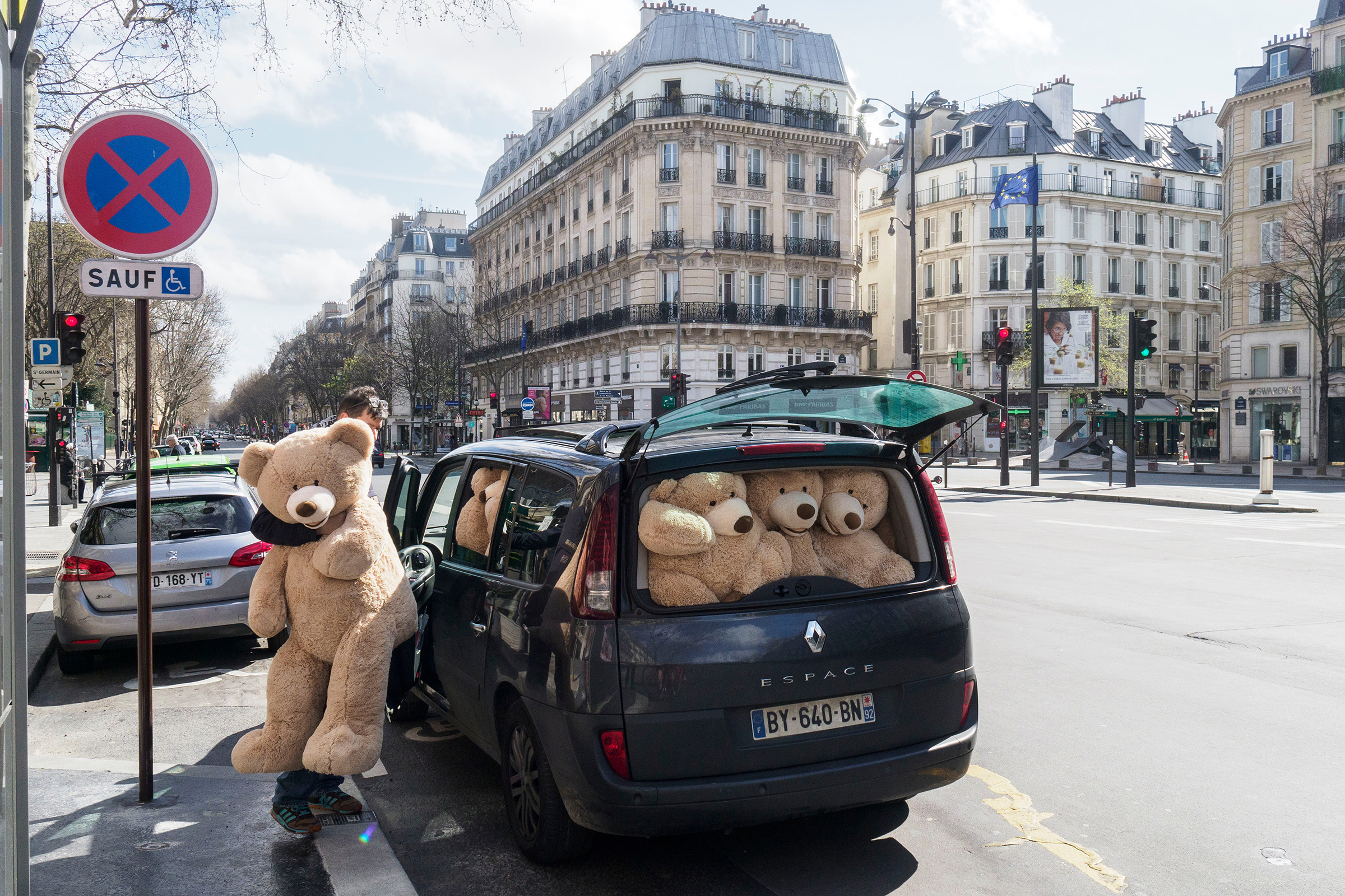 A man distributes giant teddy bears along emptied streets in Paris on March 15, the first day of the city's lockdown; nine days later, residents were allowed outside only for exercise once a day, within 1 km of their homes