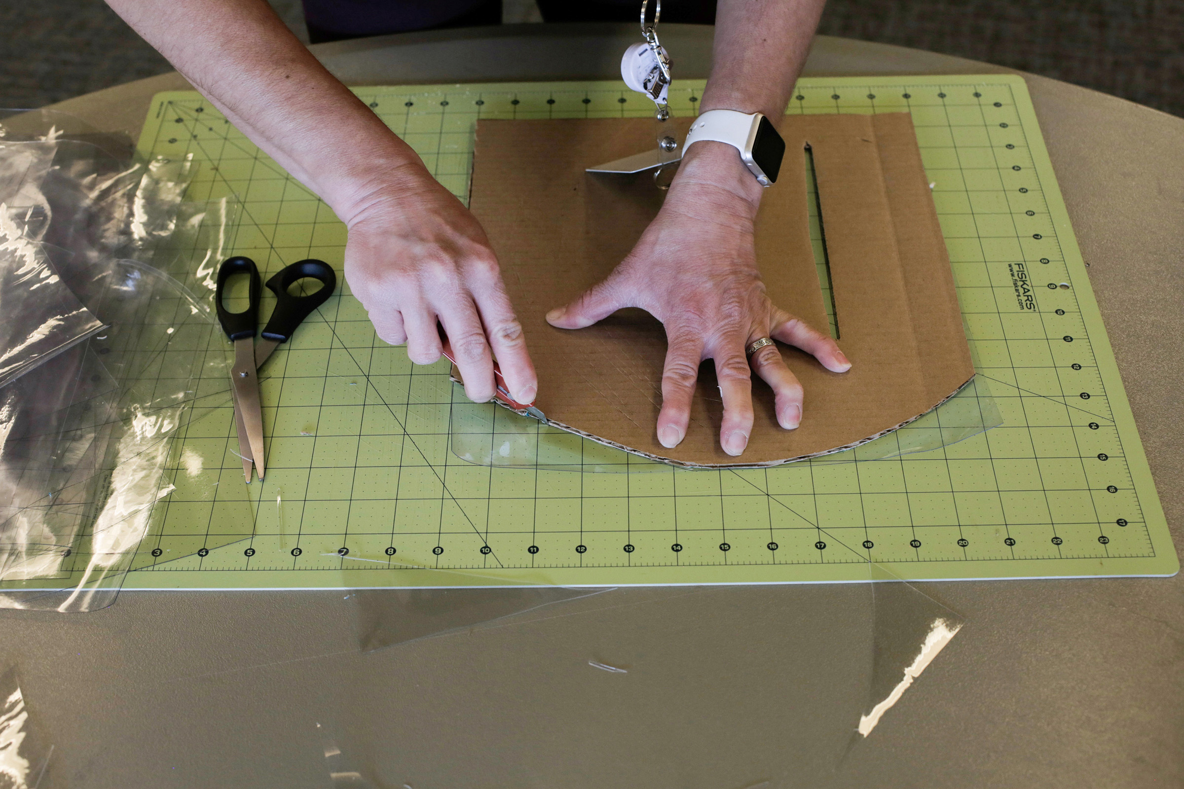 A volunteer cuts clear vinyl for assembling face shields as she and other volunteers meet an urgent need of local hospitals for personal protective equipment in Washington
