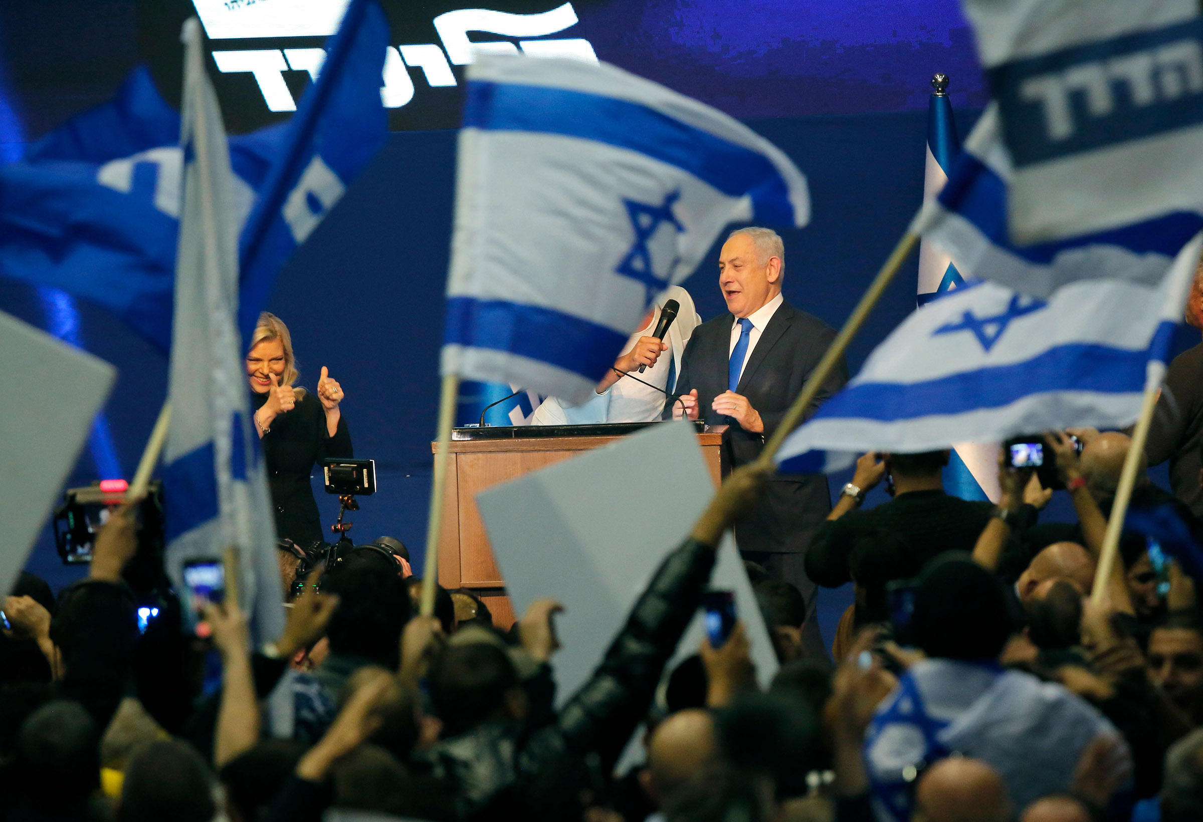 Prime Minister Benjamin Netanyahu and his wife appear before supporters at the Likud party campaign headquarters in the coastal city of Tel Aviv on March 3, 2020, after polls officially closed.