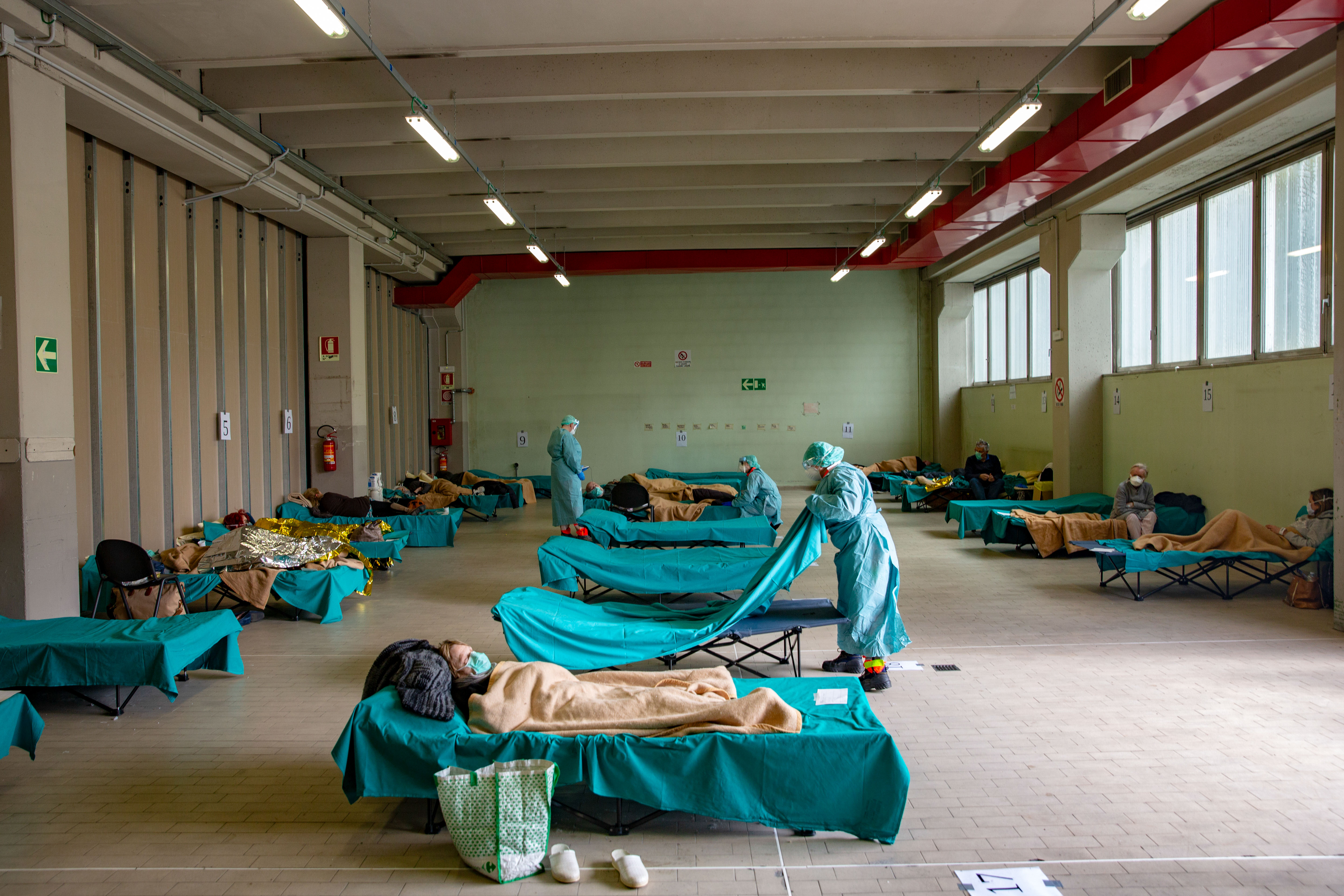 Medical personnel care for patients in an emergency temporary room, set up to ease pressure on the healthcare system, at a hospital in Brescia, Italy, on Friday, March 13, 2020.