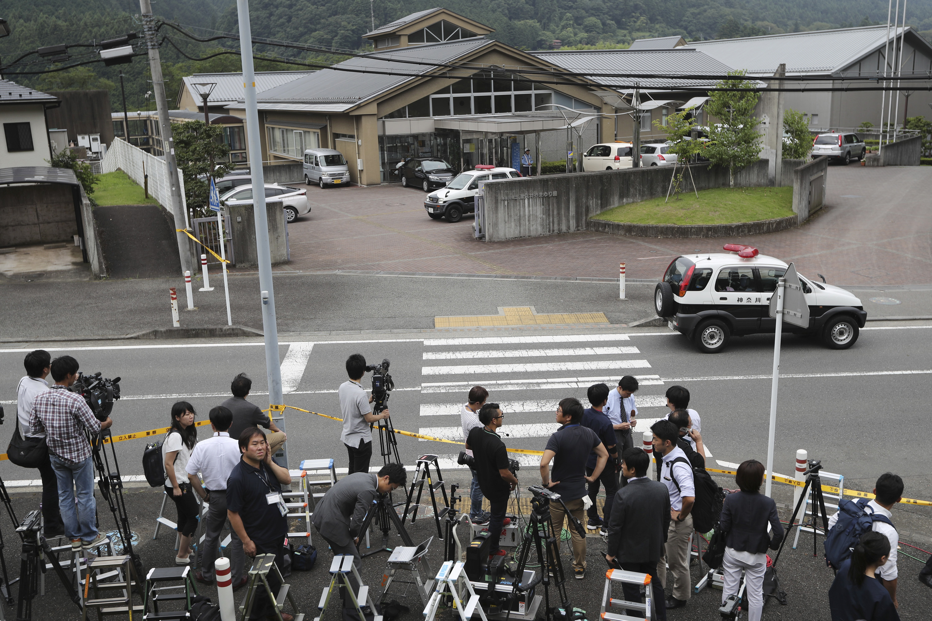 In this July 26, 2016, file photo, journalists gather in front of Tsukui Yamayuri-en, a facility for the handicapped where a former care home employee killed disabled people, in Sagamihara, outside Tokyo.