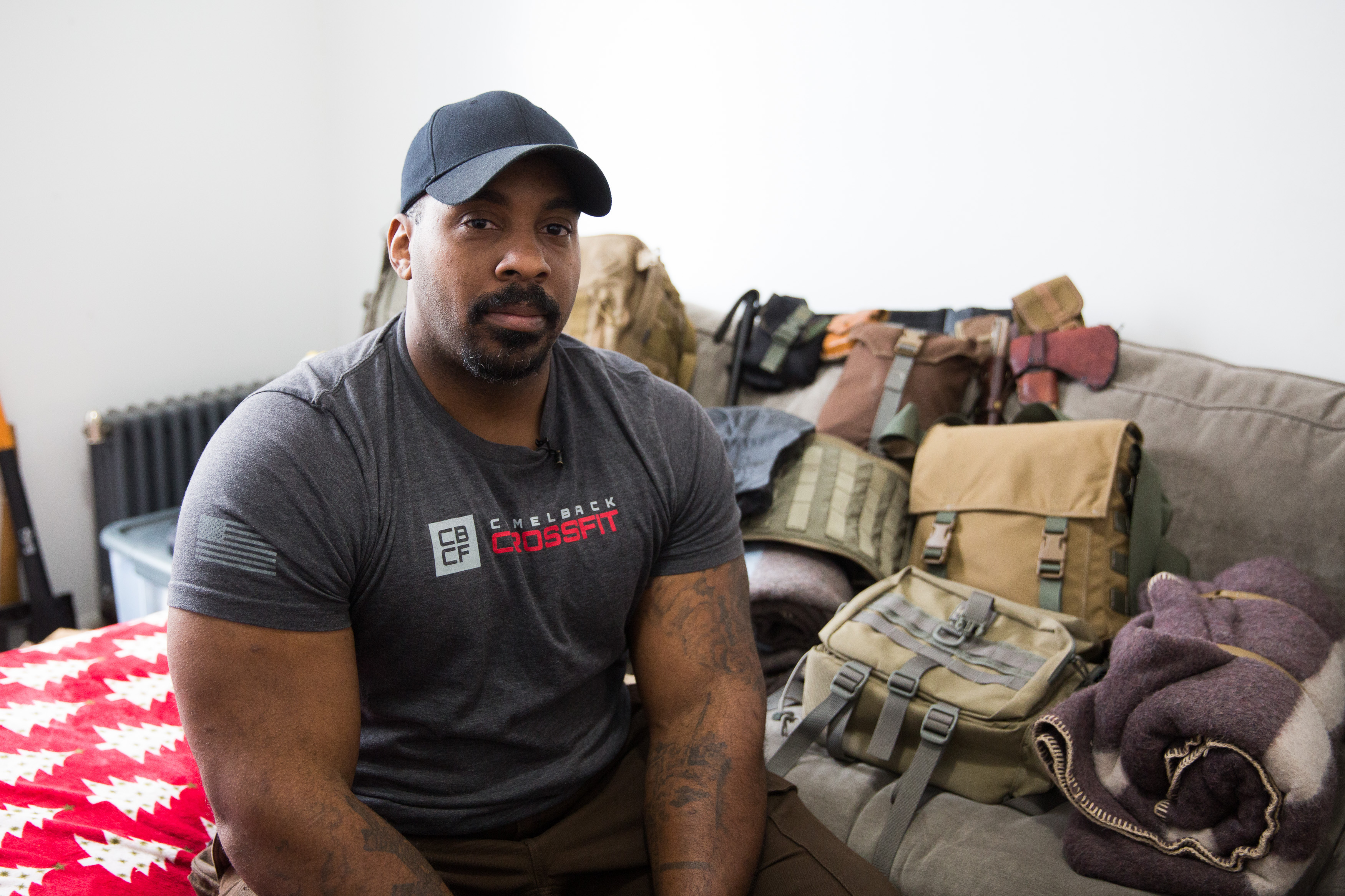Prepper Jason Charles sits in his Harlem apartment, alongside a stack of his emergency preparedness supplies on March 5, 2018 in Harlem, New York.