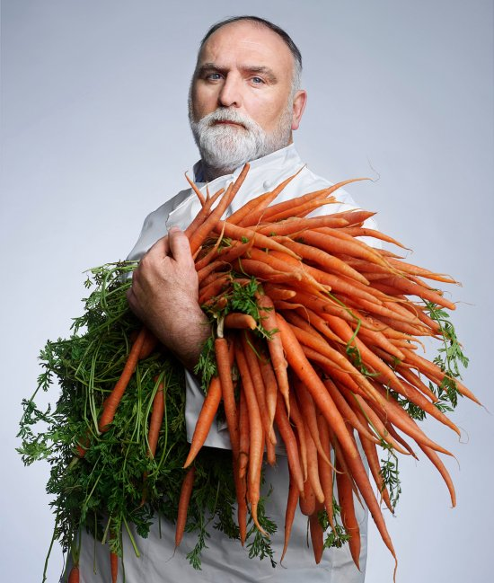 Chef José Andrés poses for a portrait while holding a large bundle of carrots