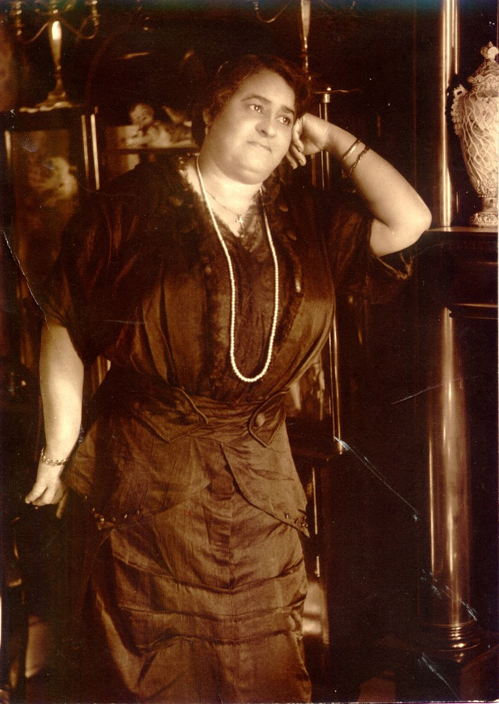 Maggie L. Walker, standing in the parlor of her home.