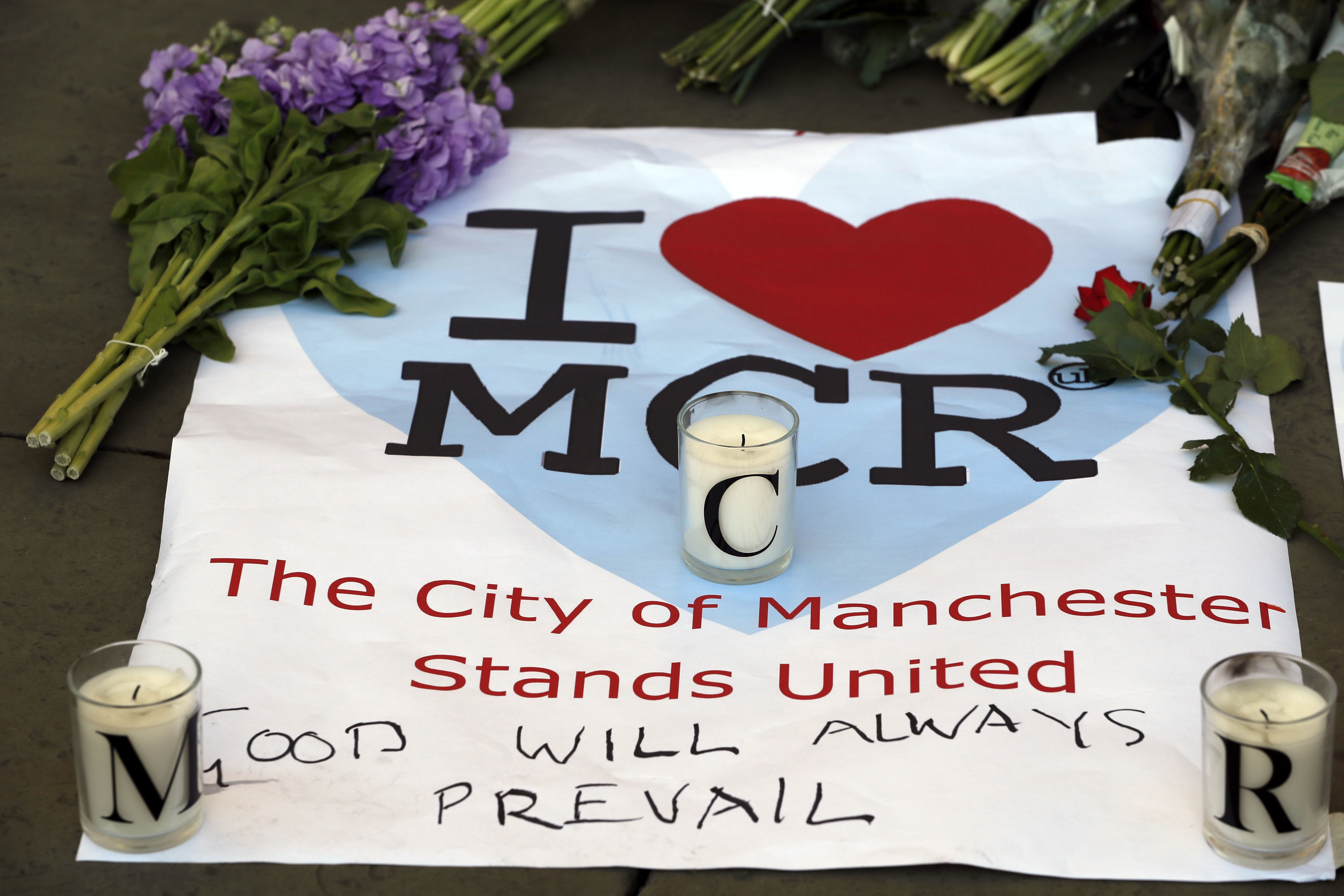 In this Tuesday May 23, 2017 file photo, a sign is seen with flowers and candles after a vigil in Albert Square, Manchester, England, the day after the suicide attack at an Ariana Grande concert that left 22 people dead.
