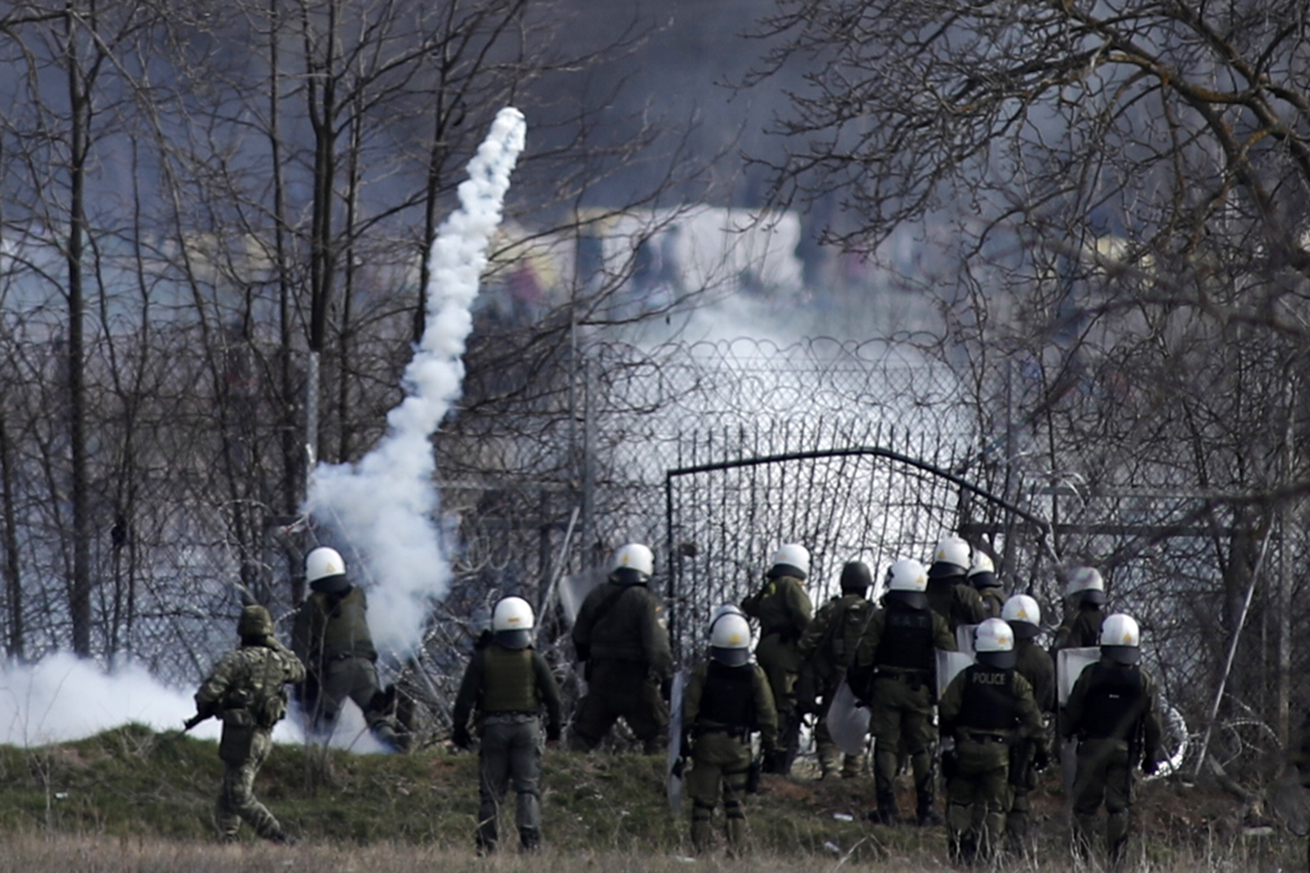 Greek police guard as migrants gather at a border fence on the Turkish side, during clashes at the Greek-Turkish border in Kastanies, Evros region, on March 7, 2020.