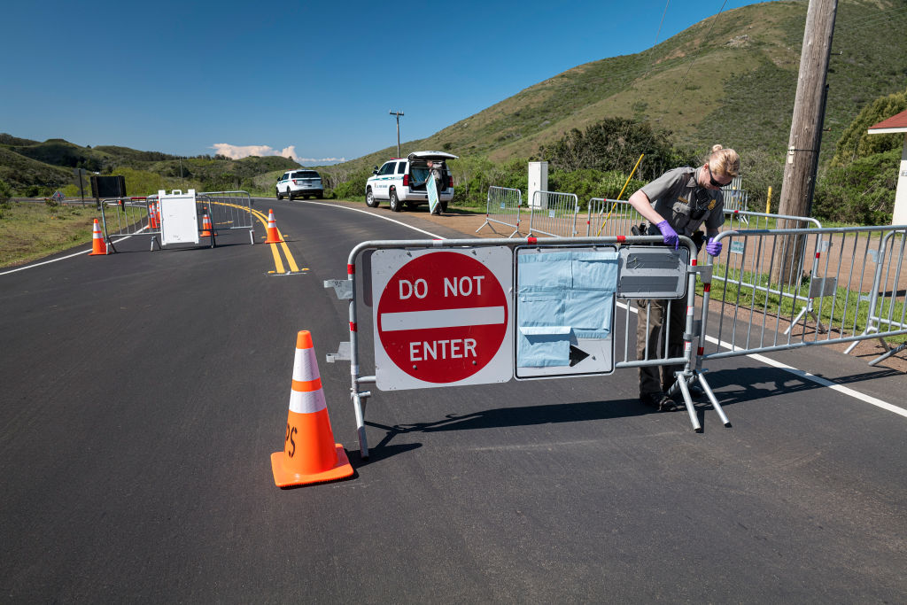 A U.S. National Park Ranger puts up a road block on Bunker Road in Sausalito, Calif., on Mar. 26, 2020.