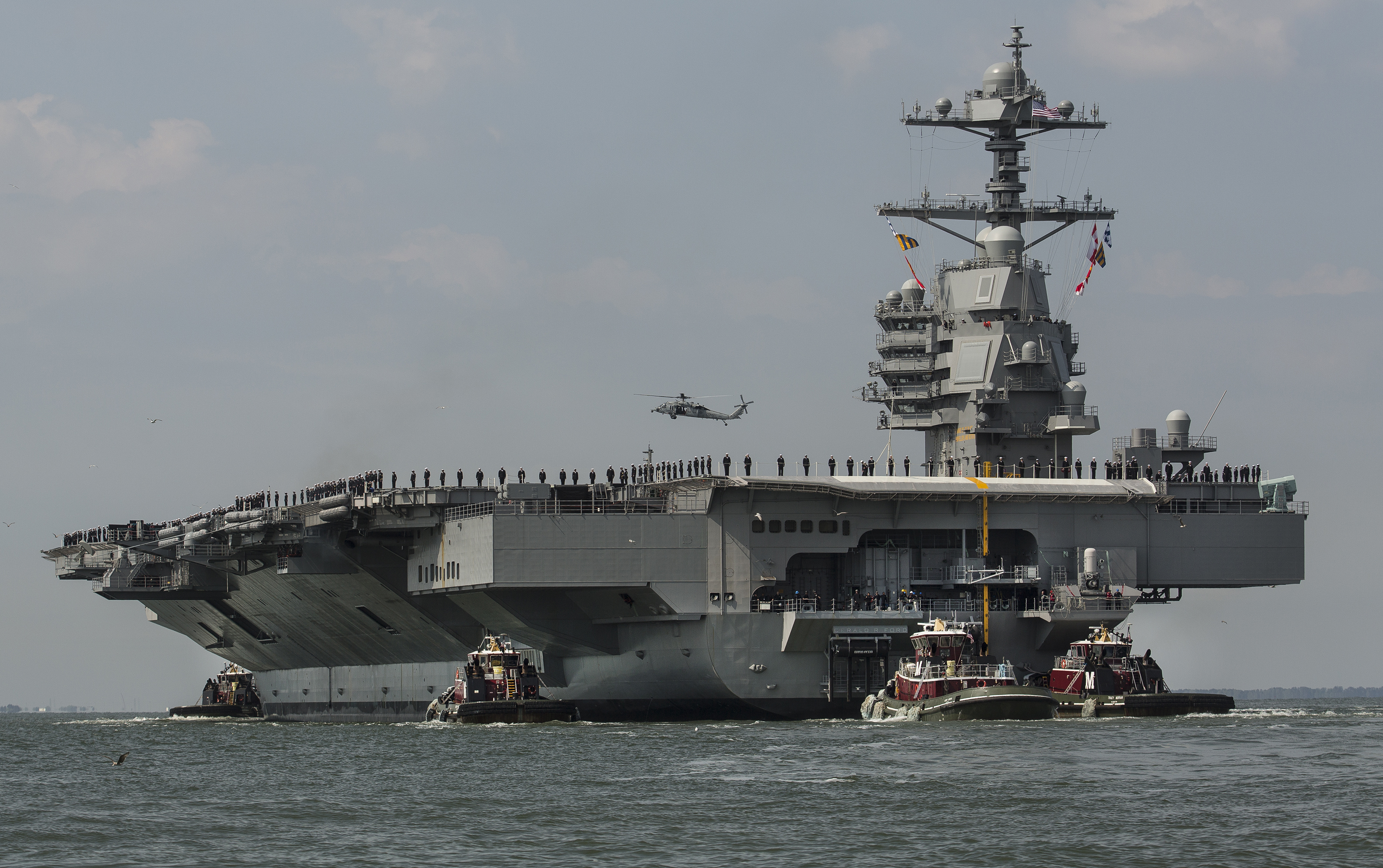 In this April 14, 2017 file photo, as crew members stand on the deck, the aircraft carrier USS Gerald R. Ford heads to the Norfolk, Va., naval station.