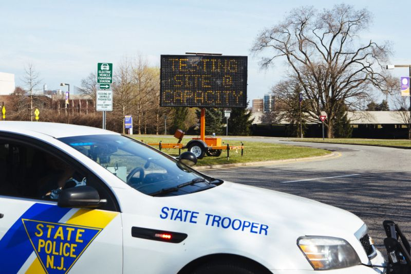 A New Jersey State Police vehicle drives in front of an electronic sign that reads Testing Site At Capacity outside a drive-through coronavirus testing facility at Bergen Community College in Paraumus, New Jersey, U.S., on Friday, March 20, 2020.